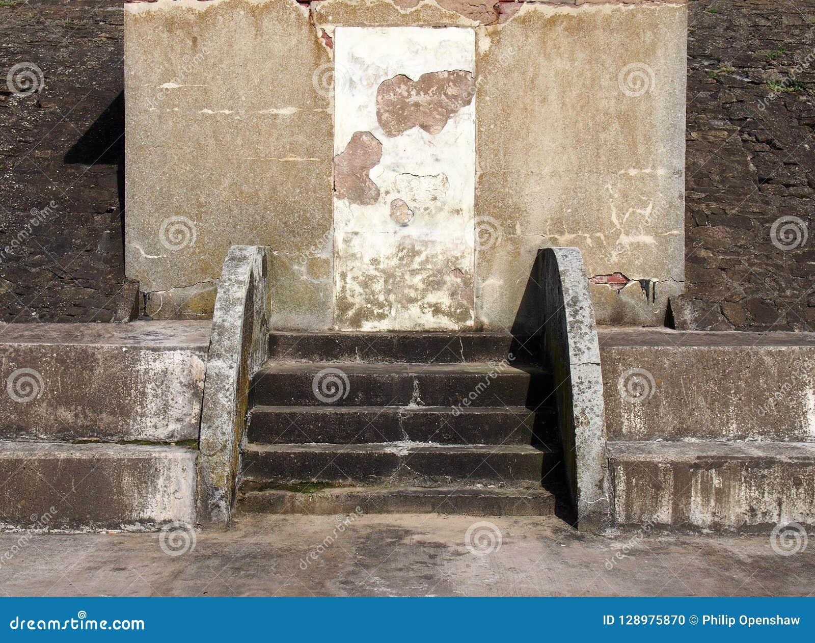 与一个封锁的门的老被放弃的具体避难所与破裂的被修理的步和被修补的被腐蚀的墙壁在阳光和阴影下