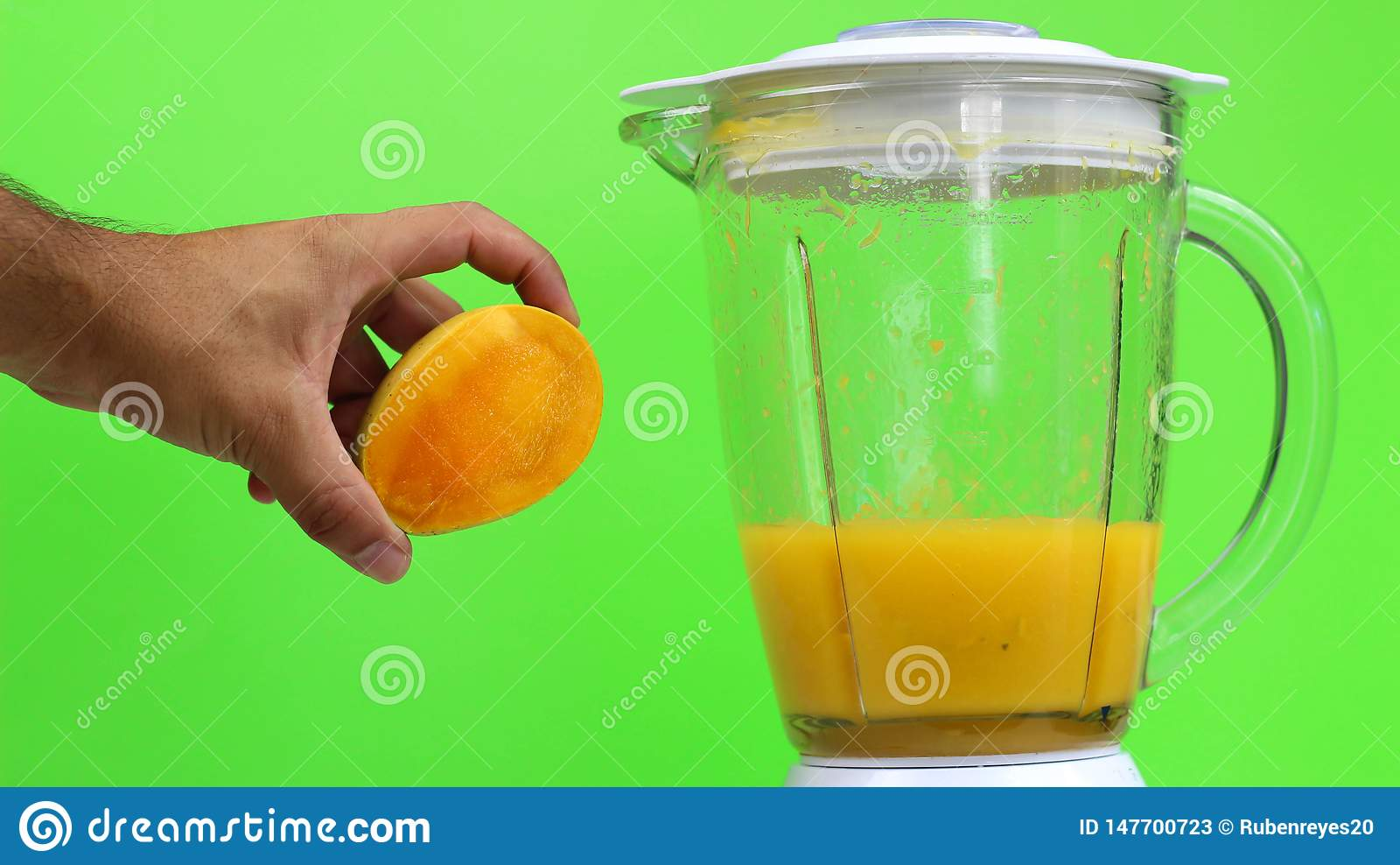 与一台搅拌器的芒果汁,在绿色背景