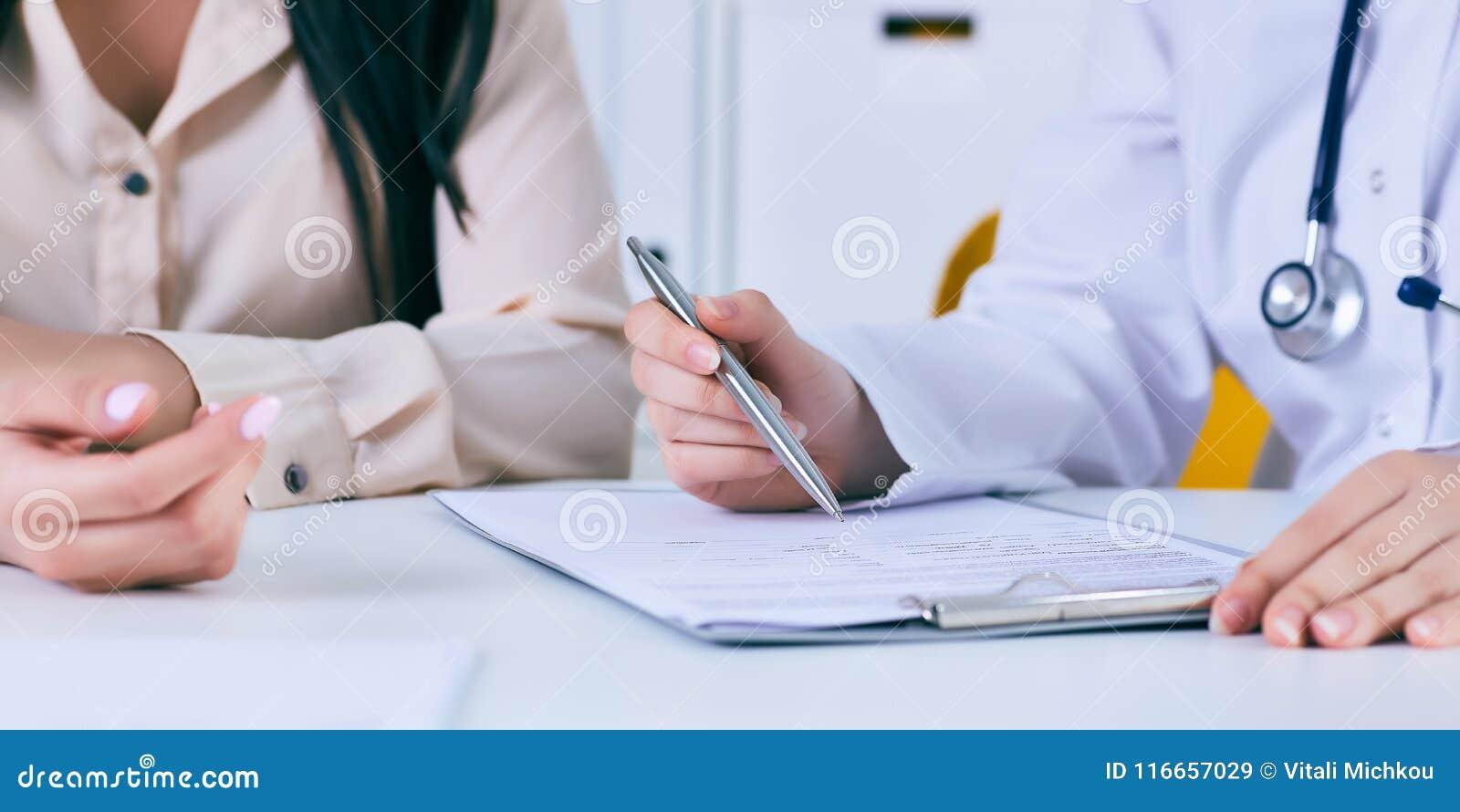 与一名患者的女性医生会谈在办公室,她给一张处方妇女 移交桌
