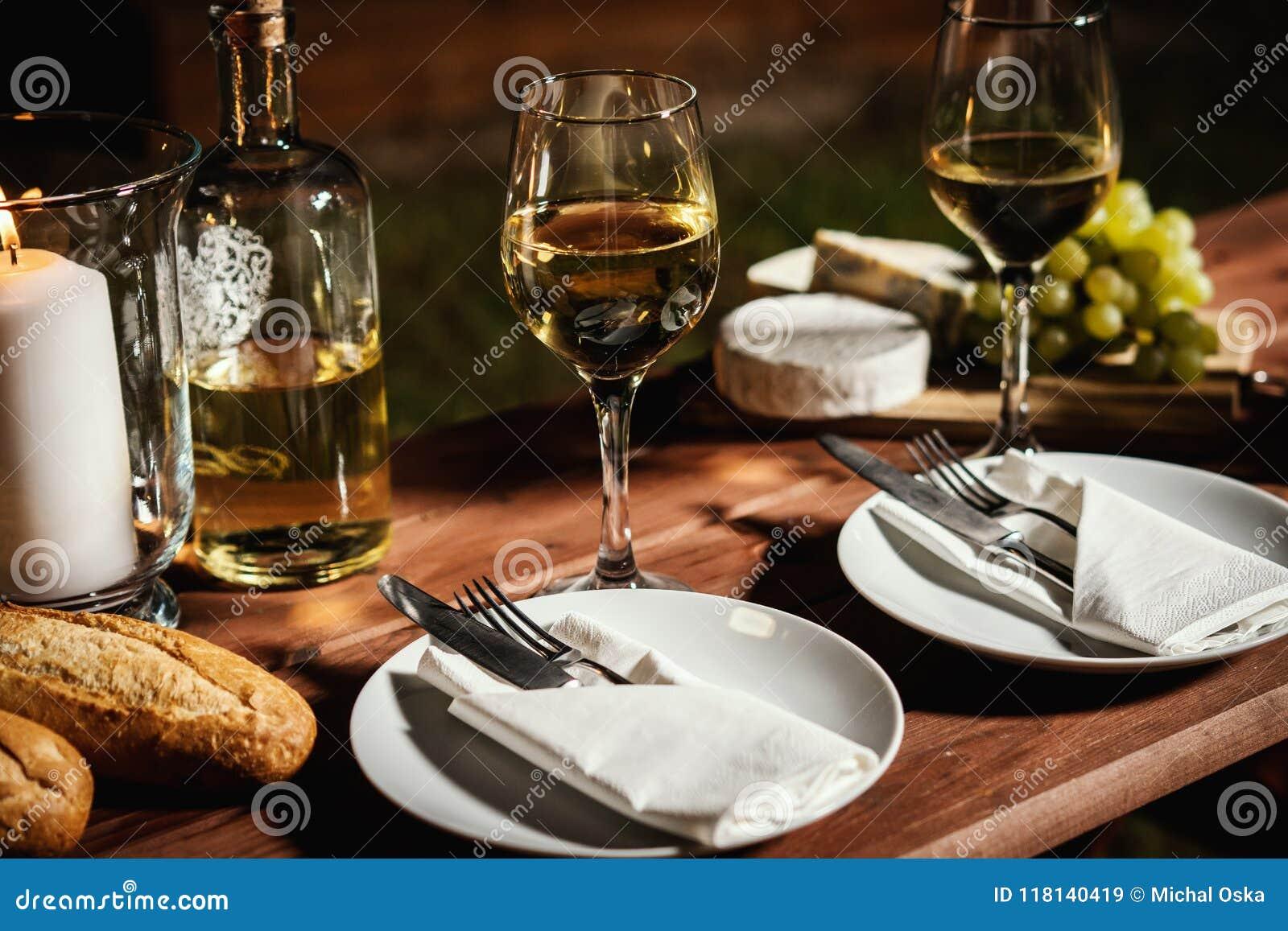 与一杯的浪漫晚餐酒和快餐在一张老木桌上