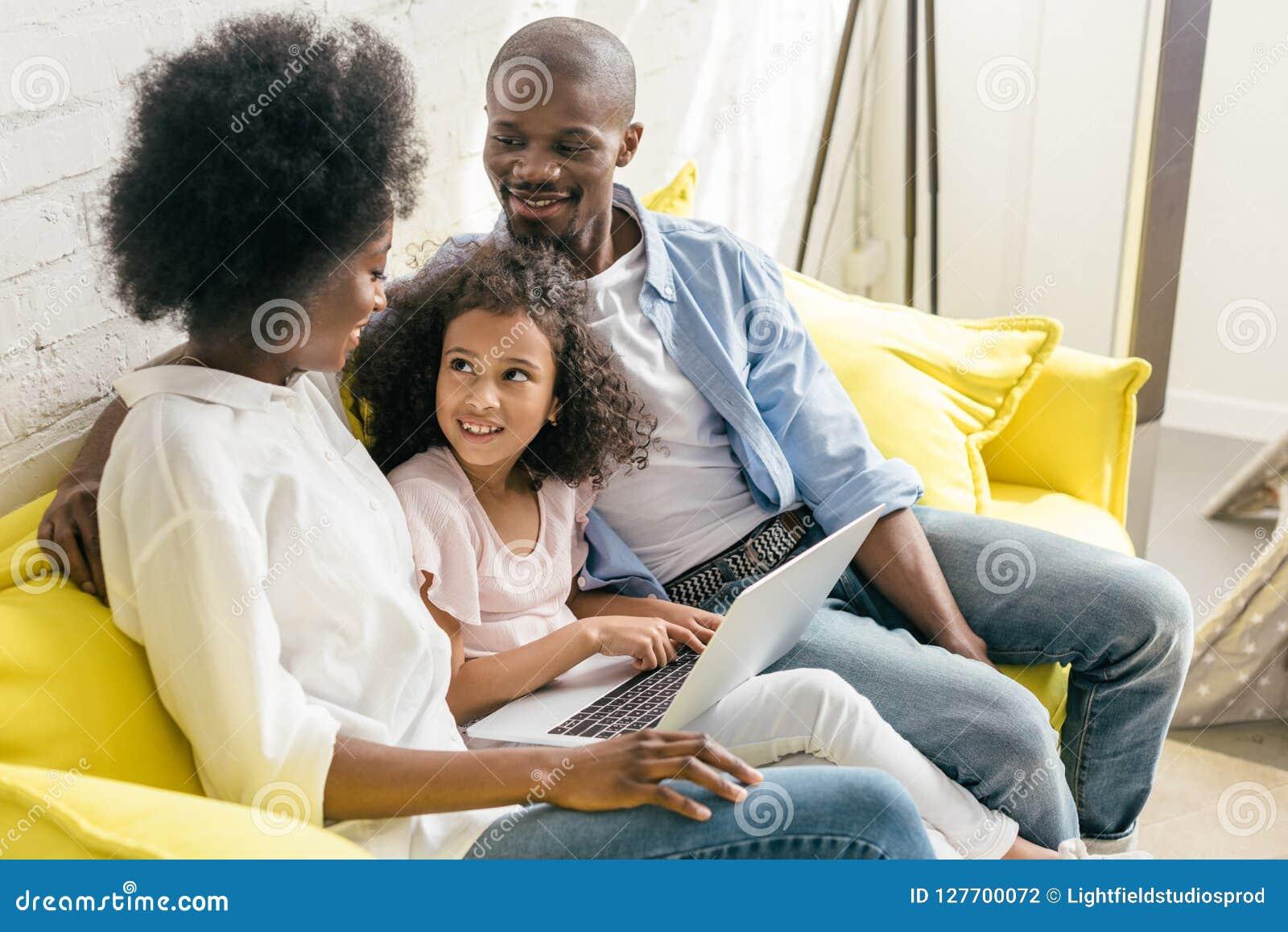 与一起基于沙发的膝上型计算机的非裔美国人的家庭
