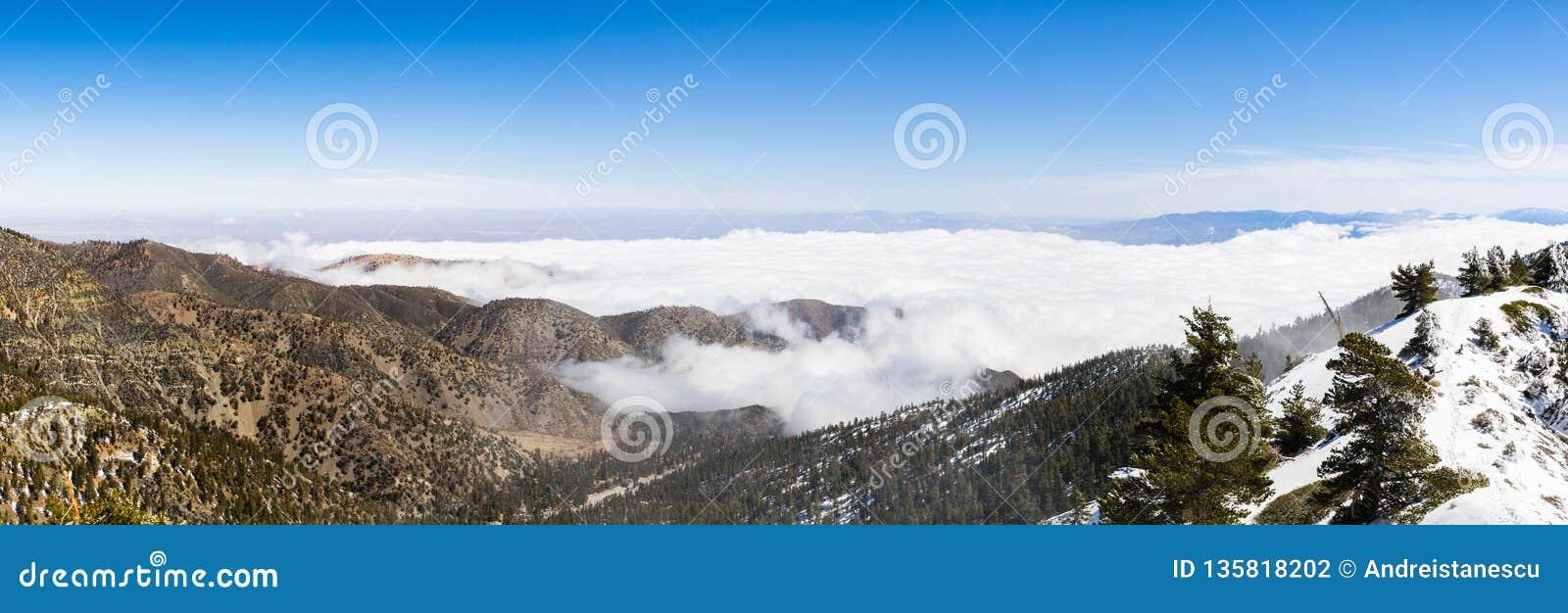 与下落的雪和白色云彩海的晴朗的冬日在足迹的对Mt圣安东尼奥(Mt鲍尔迪),洛杉矶县,