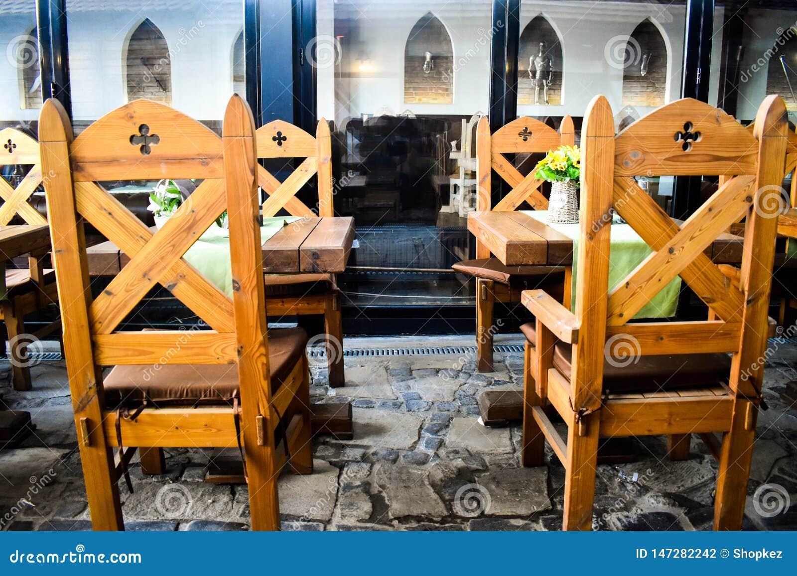 与中世纪装饰的古老木椅子在有许多封建年龄装饰元素的葡萄酒餐馆