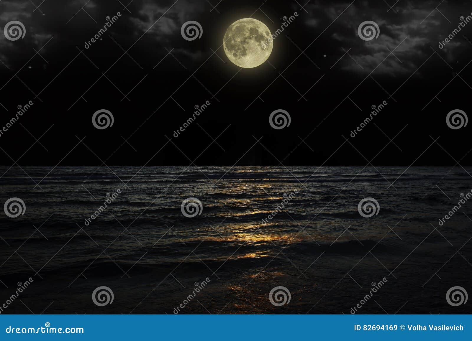 与云彩和满月的美丽的不可思议的蓝色夜空在水中担任主角反射
