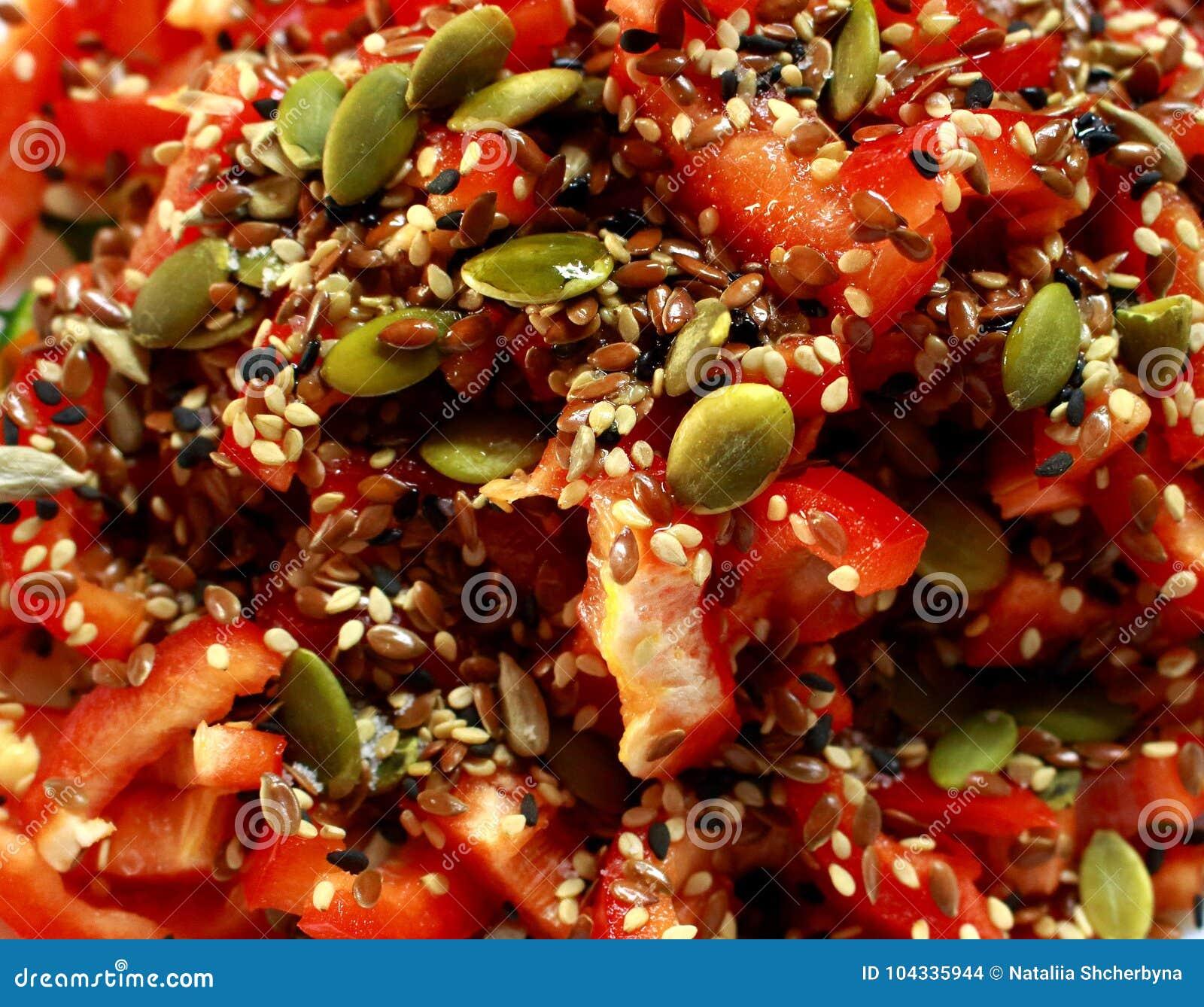 与五颜六色的向日葵种子的明亮的蕃茄沙拉作为新健康vegeterian食物背景