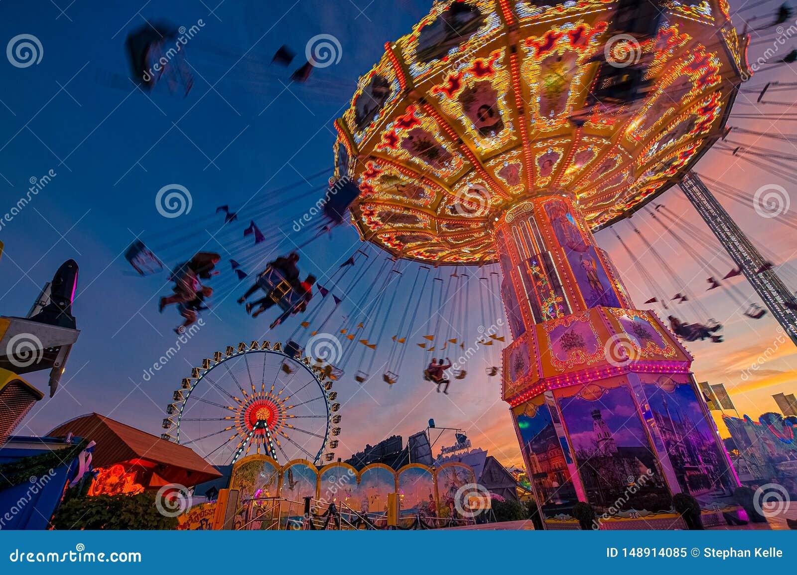 与人silhouttes的链carusel获得乐趣在慕尼黑啤酒节在慕尼黑