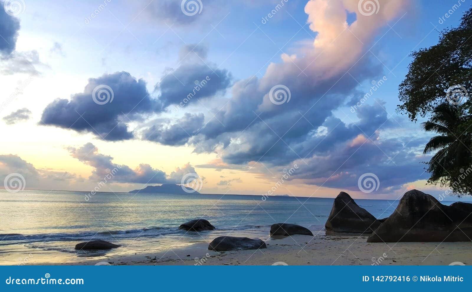 与令人惊讶的天空和岩石的平安的塞舌尔海滩日落