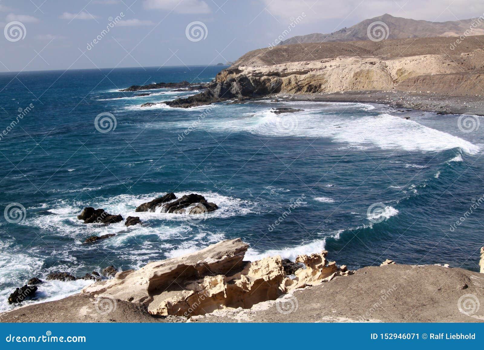 与令人惊讶的峭壁和蓝色风大浪急的海面的惊人自然观点费埃特文图拉岛,加那利群岛,西班牙西北海岸的