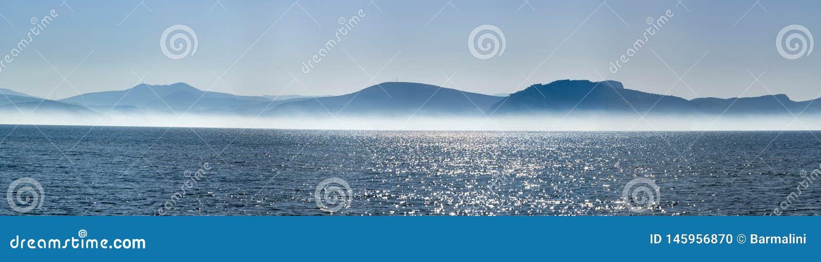 与低雾云彩的海景在海水在与太阳光的清早