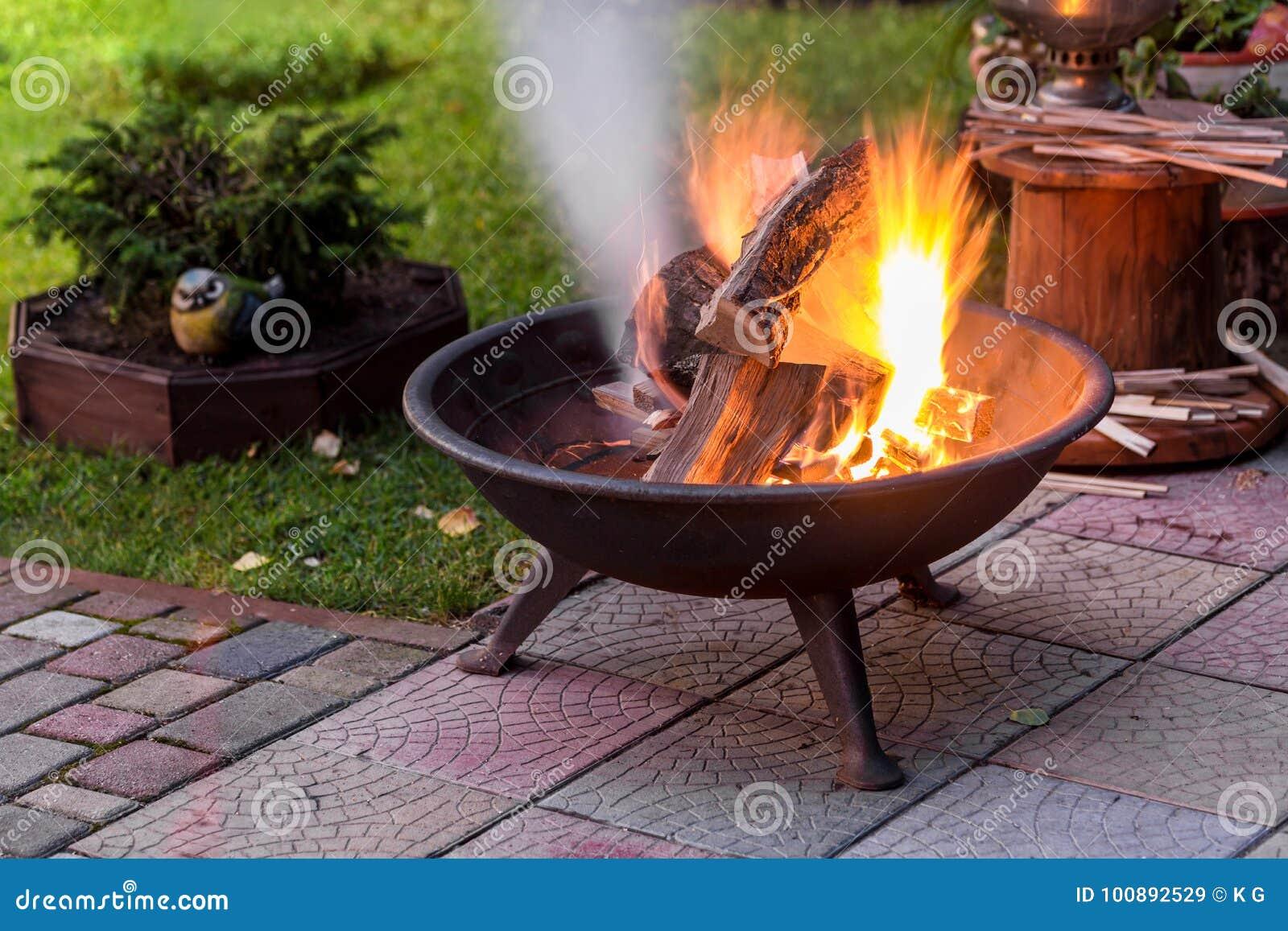 与做火花和烟的明亮的灼烧的木柴的一个便携式的壁炉在后院或庭院在房子附近 eveni的一个地方