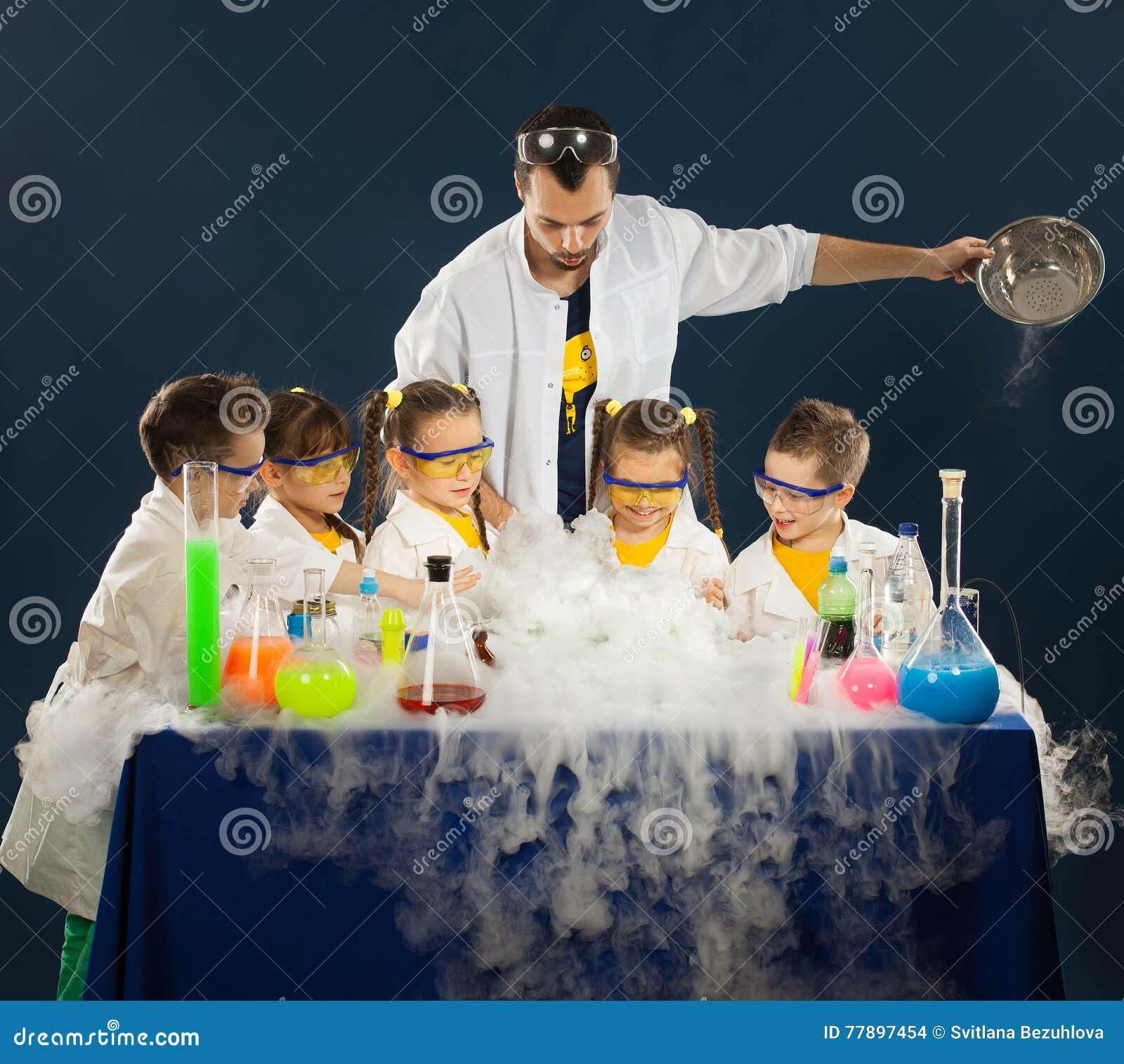 与做科学的科学家的愉快的孩子在实验室里试验
