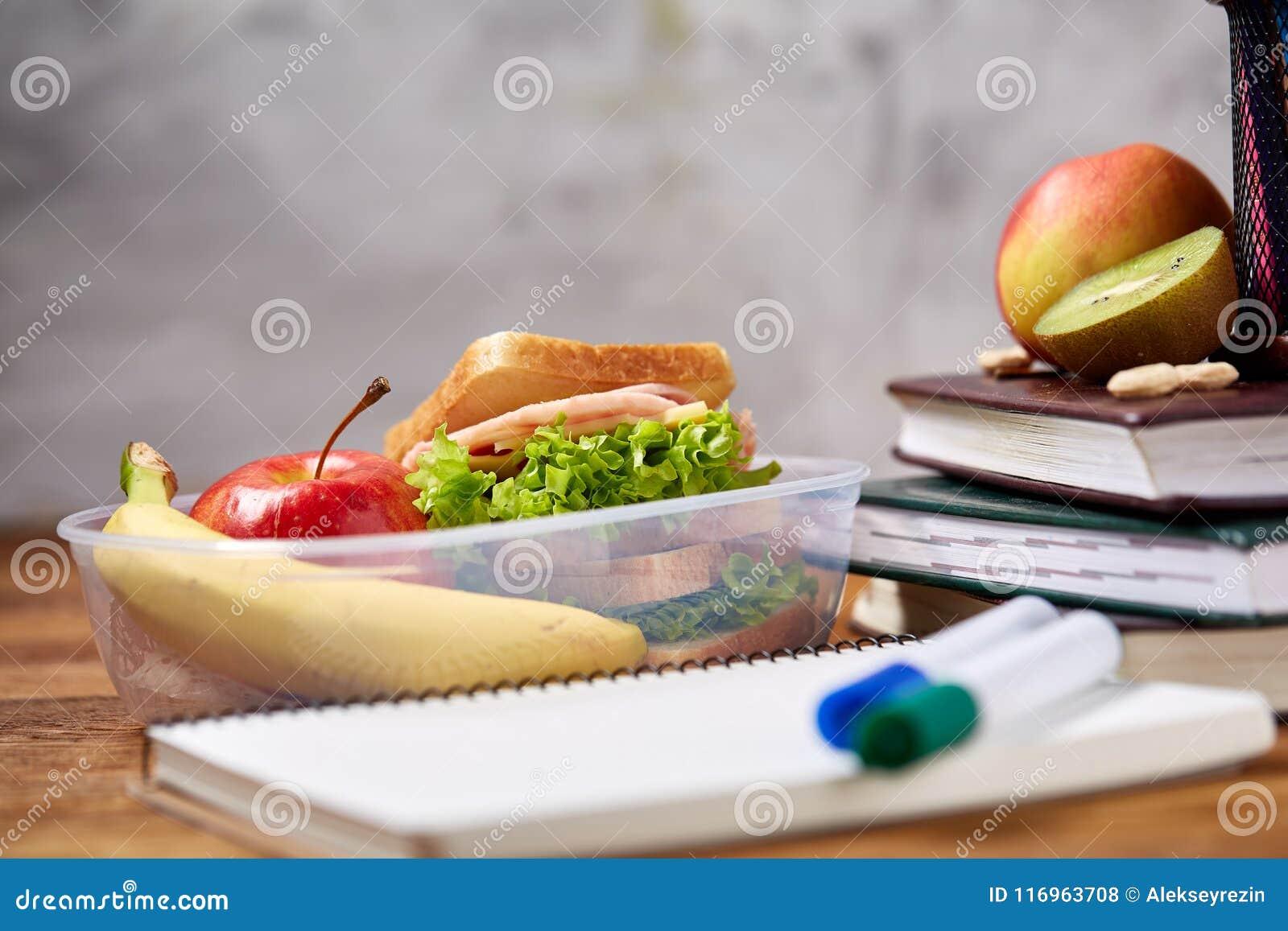 与健康午餐盒的学校午餐断裂和在木书桌,选择聚焦上的学校用品的概念