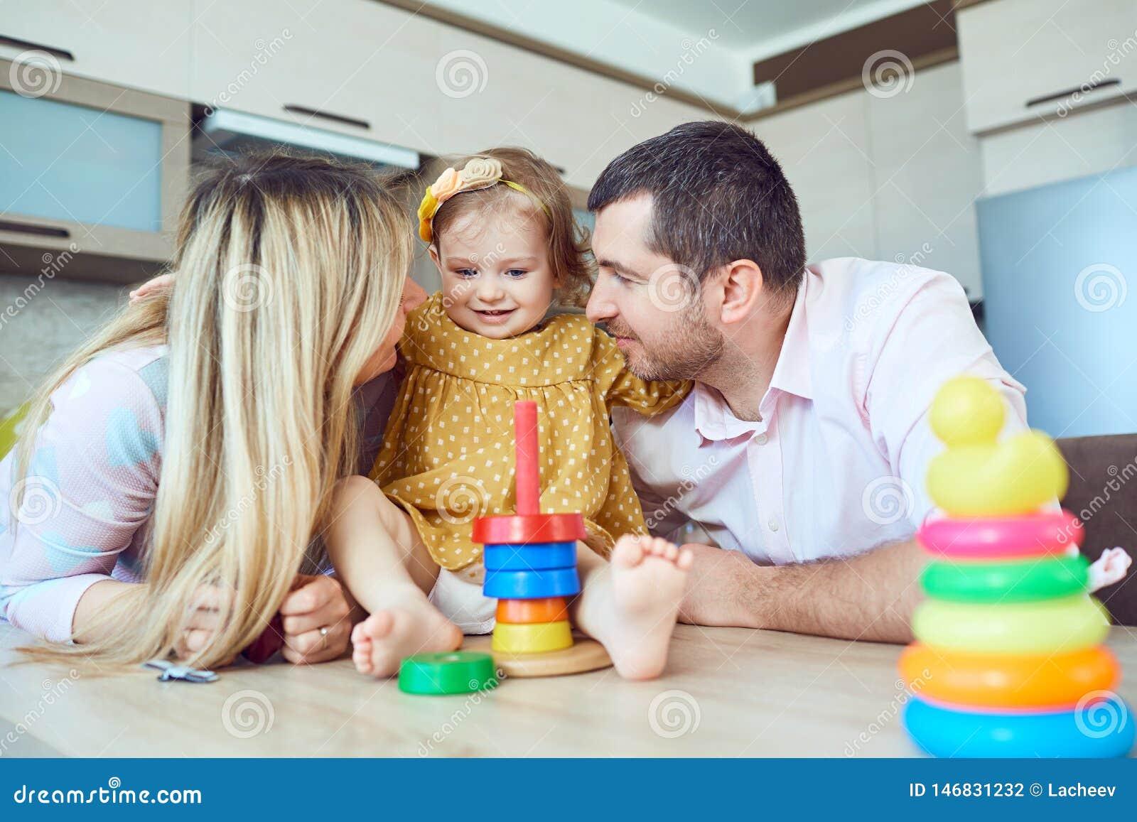 与儿童游戏坐在桌上的棋的一个家庭