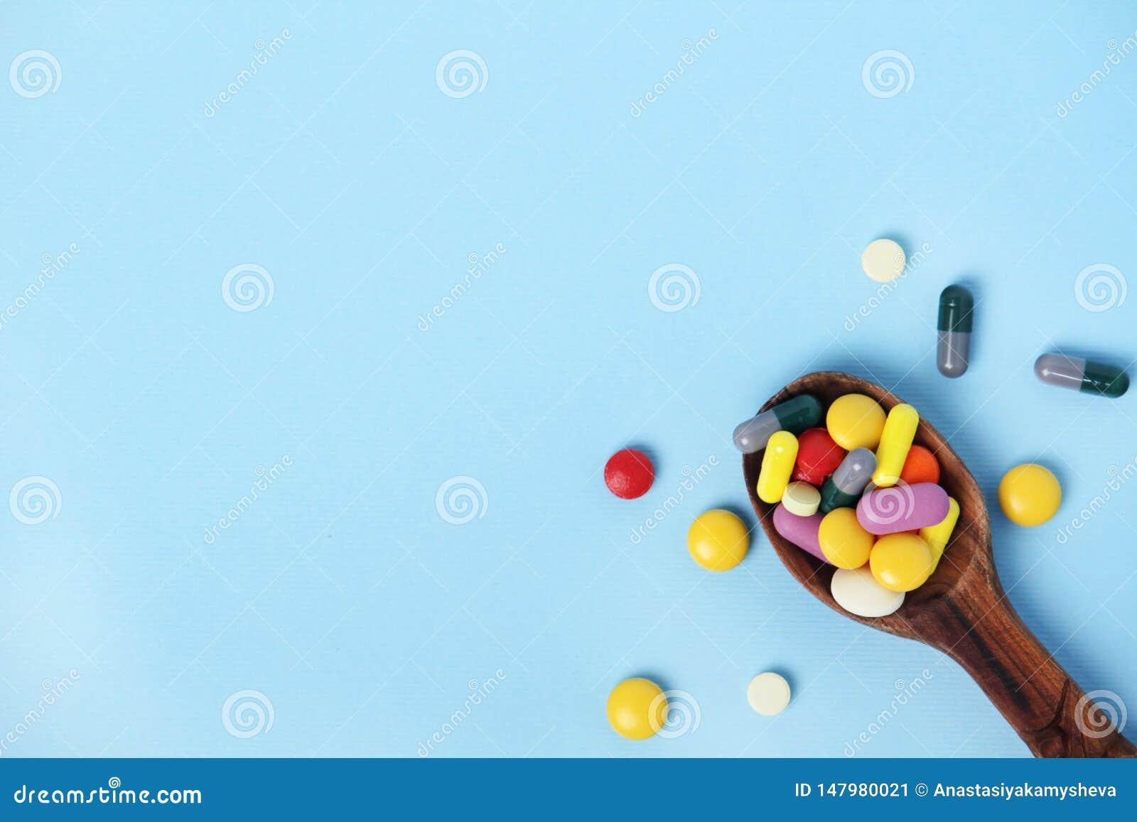 与充分匙子的明亮的背景医疗药片