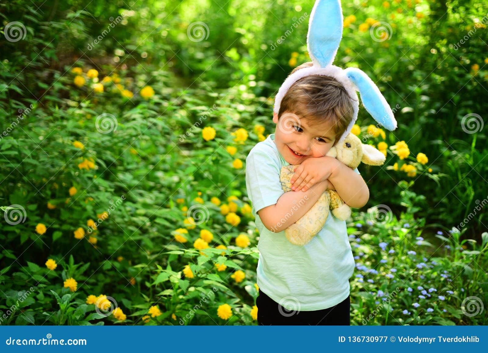 与兔宝宝耳朵的兔子孩子 野兔玩具 蛋狩猎春天假日 爱复活节 家庭假日 小男孩孩子以绿色