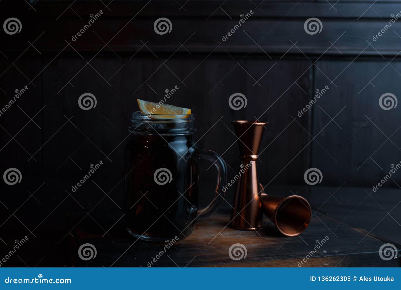 与冰、威士忌酒和可口可乐,柠檬切片的酒精鸡尾酒在一张木桌上站立在餐馆在金属旁边