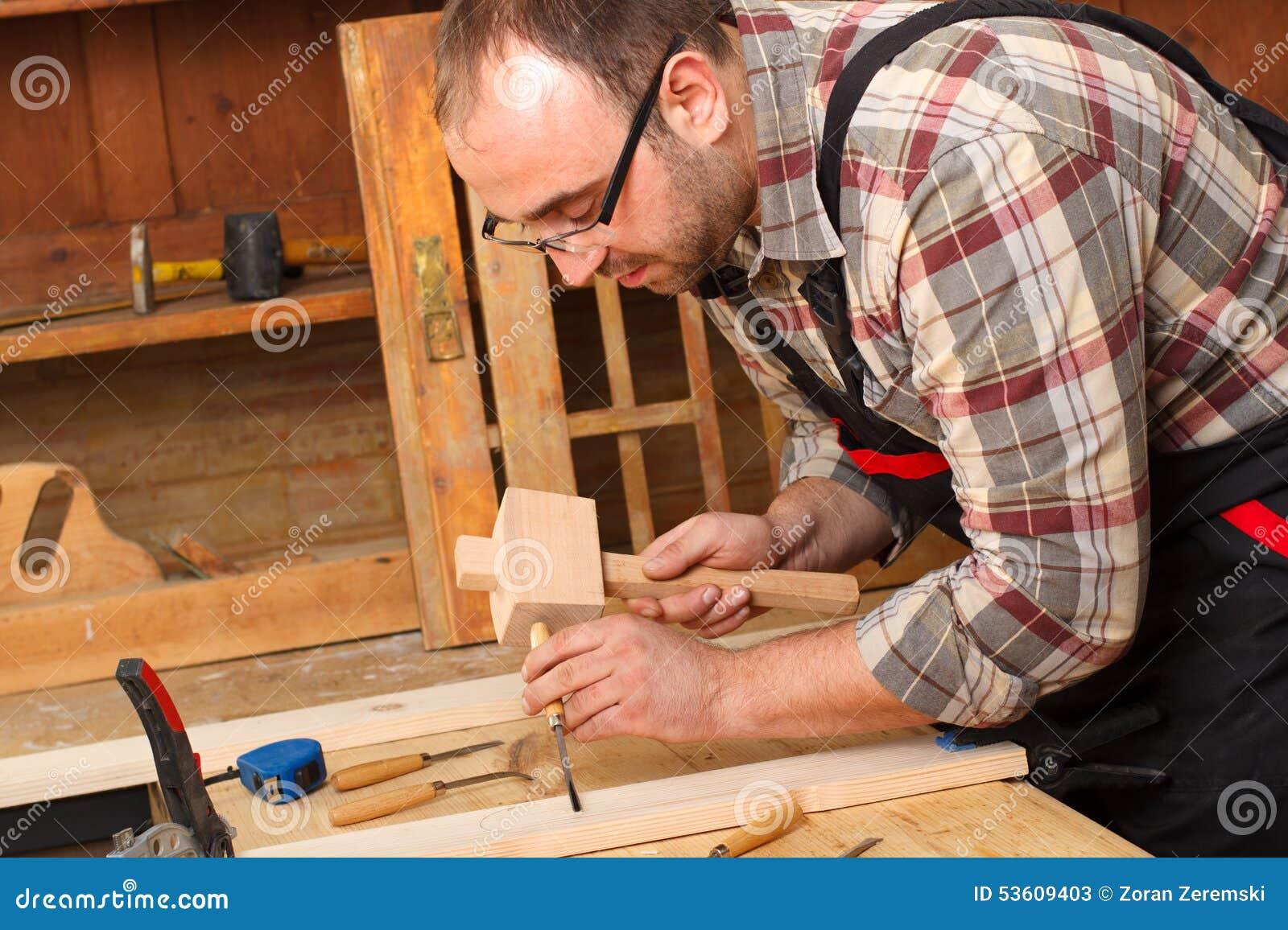 与凿子一起使用和雕刻工具的木匠的特写镜头