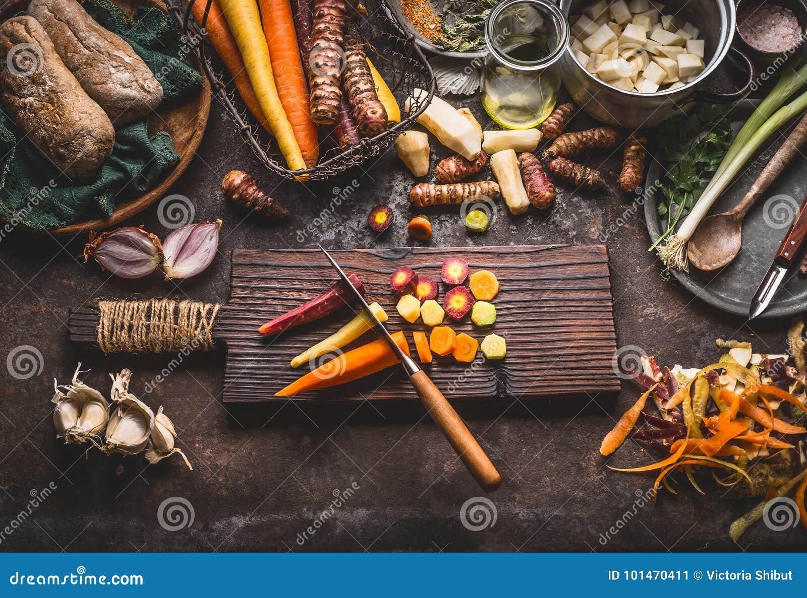 与刀子的五颜六色的切的红萝卜在土气厨房用桌背景的木切板与根菜类成份为