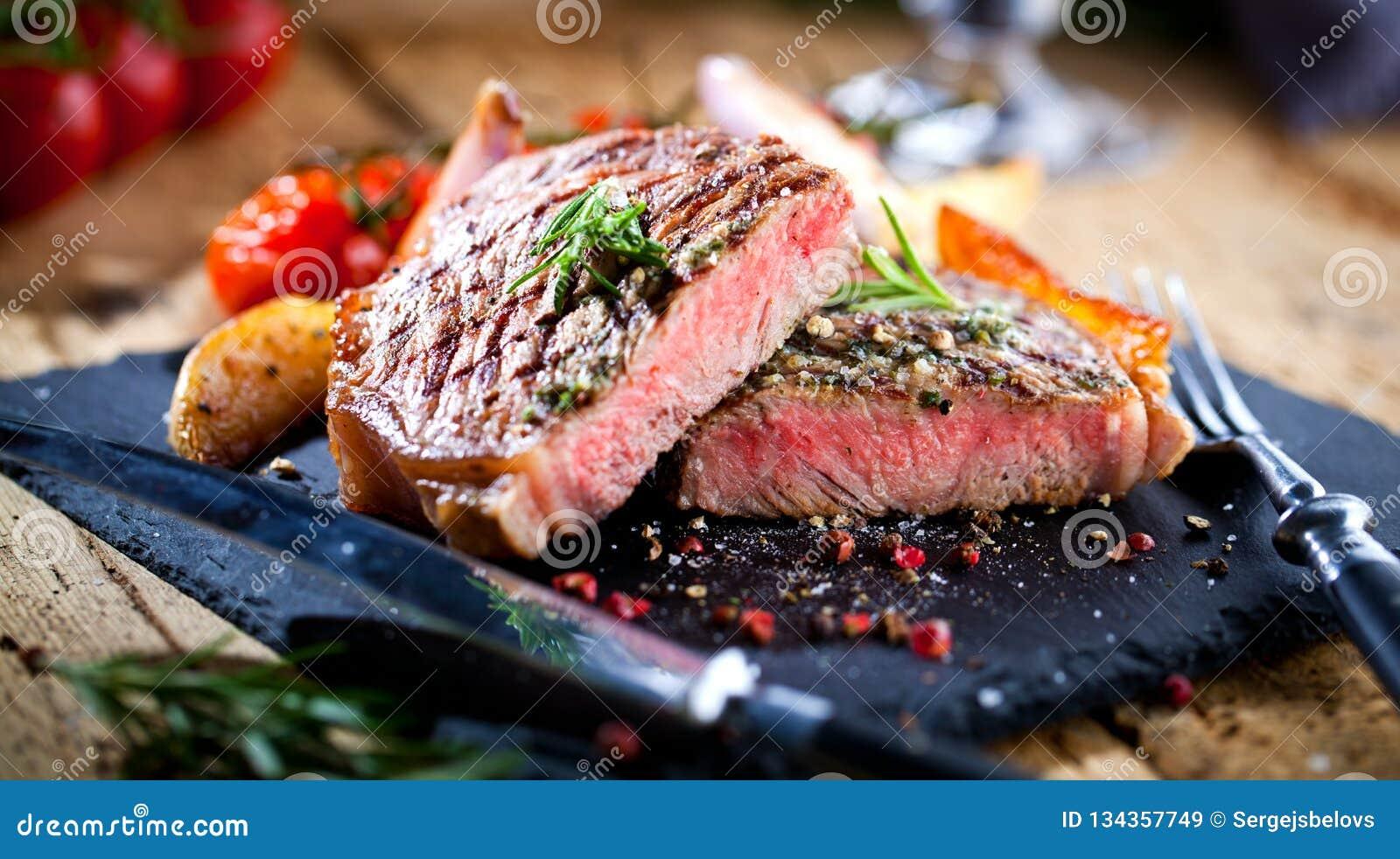 与刀子的切的烤肉烤肉雕刻在黑石板岩的牛排Striploin和叉子集合