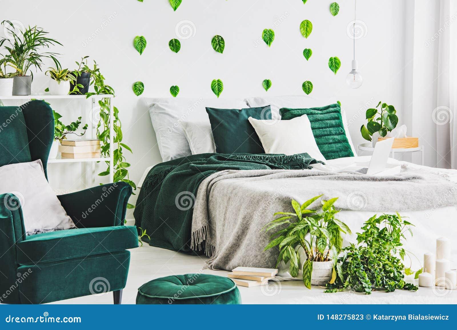 与加长型的床的白色卧室内部与灰色nd鲜绿色卧具、都市密林和绿色叶子在墙壁上