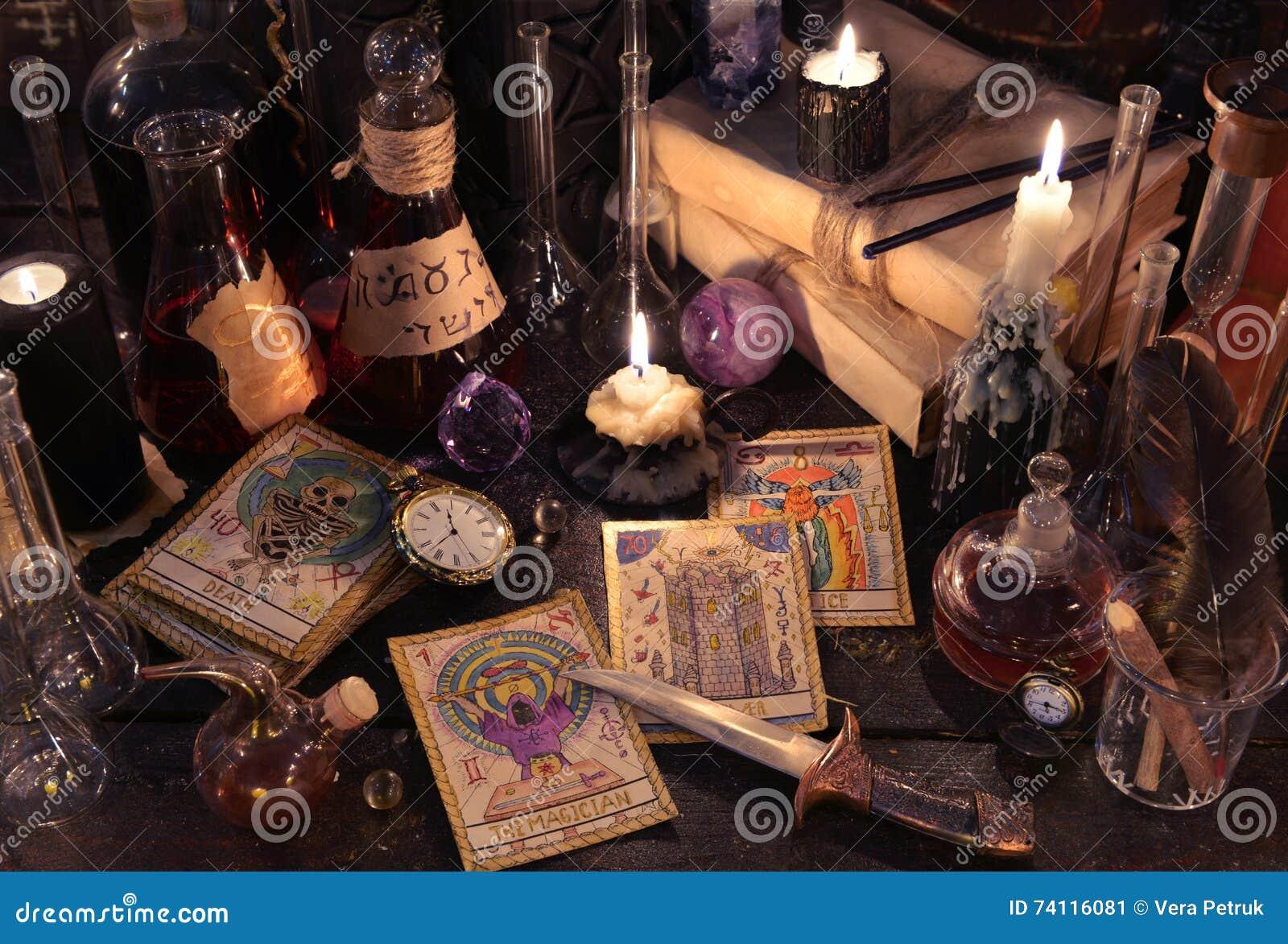 与占卜用的纸牌、刀子、书和蜡烛的静物画在巫婆桌上