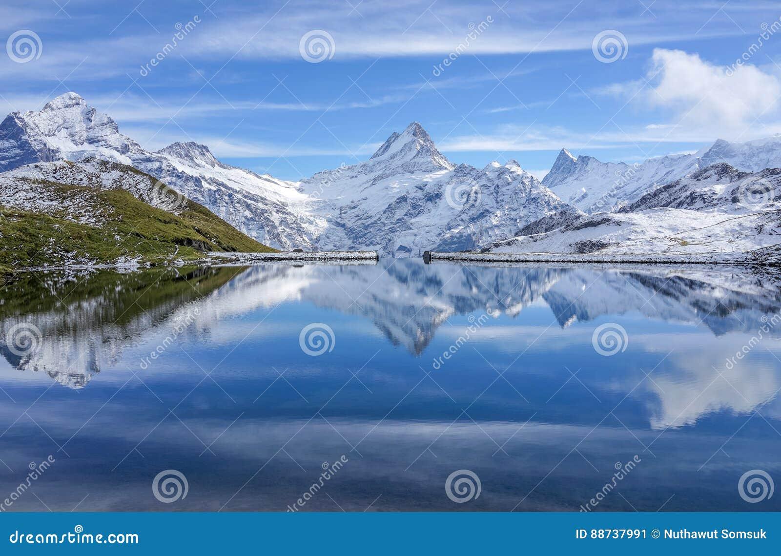 与反射的雪山在湖和明白蓝天