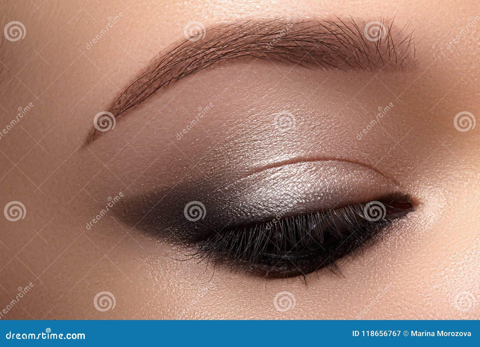 与发烟性猫眼构成的美丽的宏观眼睛 化妆用品和构成 时尚脸特写镜头与划线员,眼影膏的
