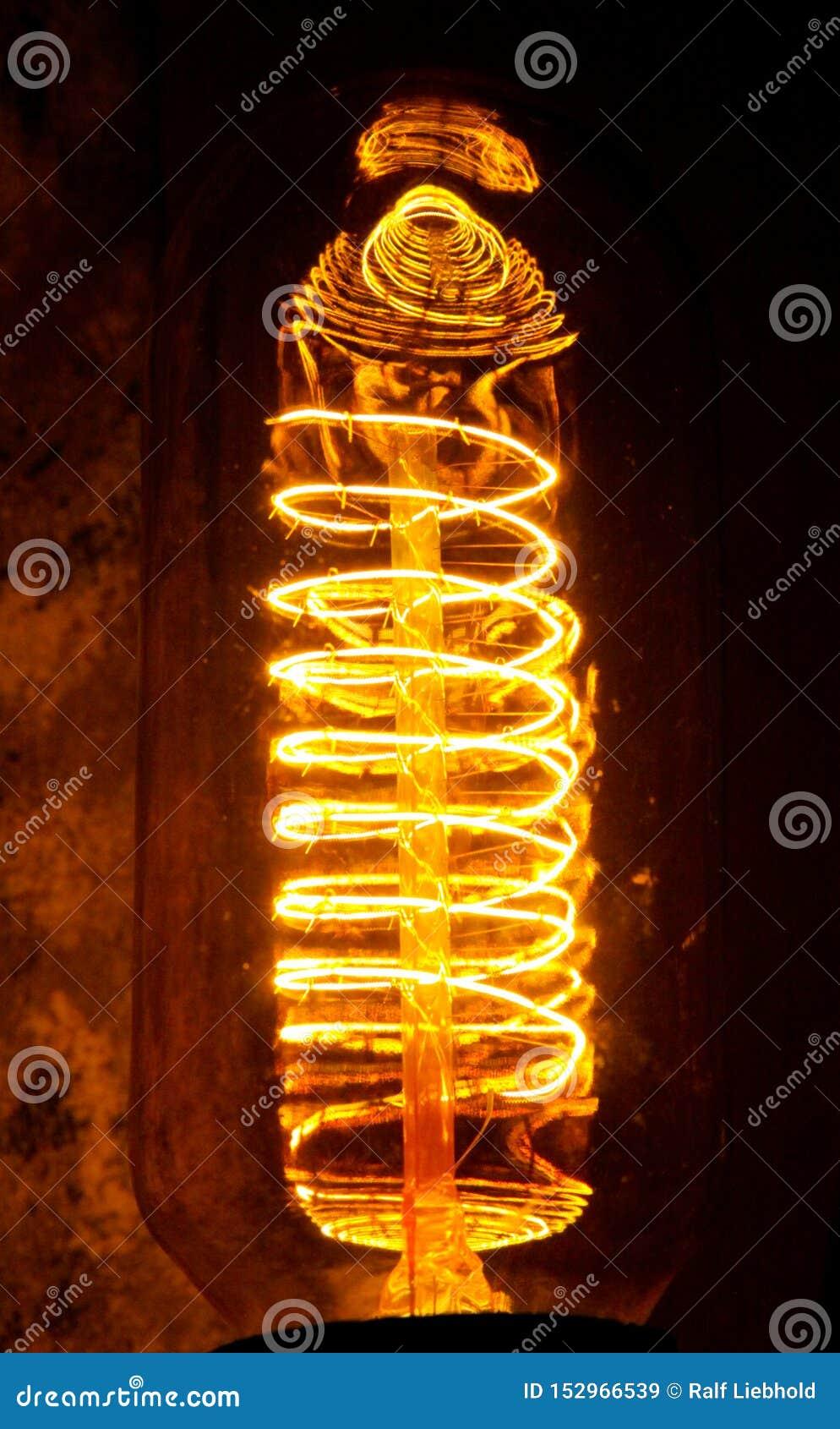 与可看见的发光的导线的被修补的经典白炽爱迪生电灯泡夜