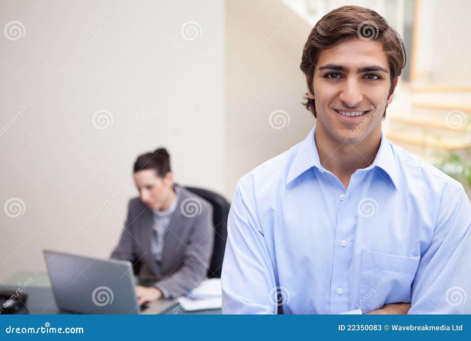 与同事的微笑的生意人她的在他之后的膝上型计算机的