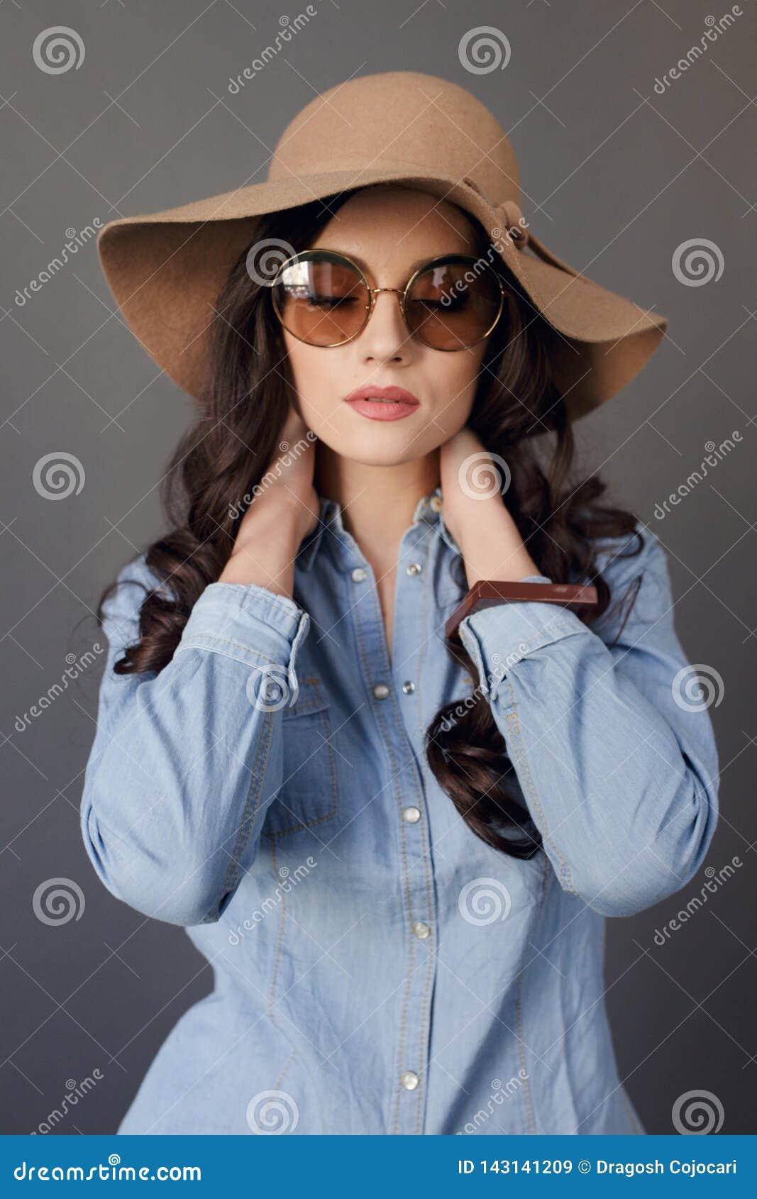 与圆的太阳镜,卷发的肉欲的深色的模型,佩带在牛仔裤衬衣和米黄帽子,接触他的脖子