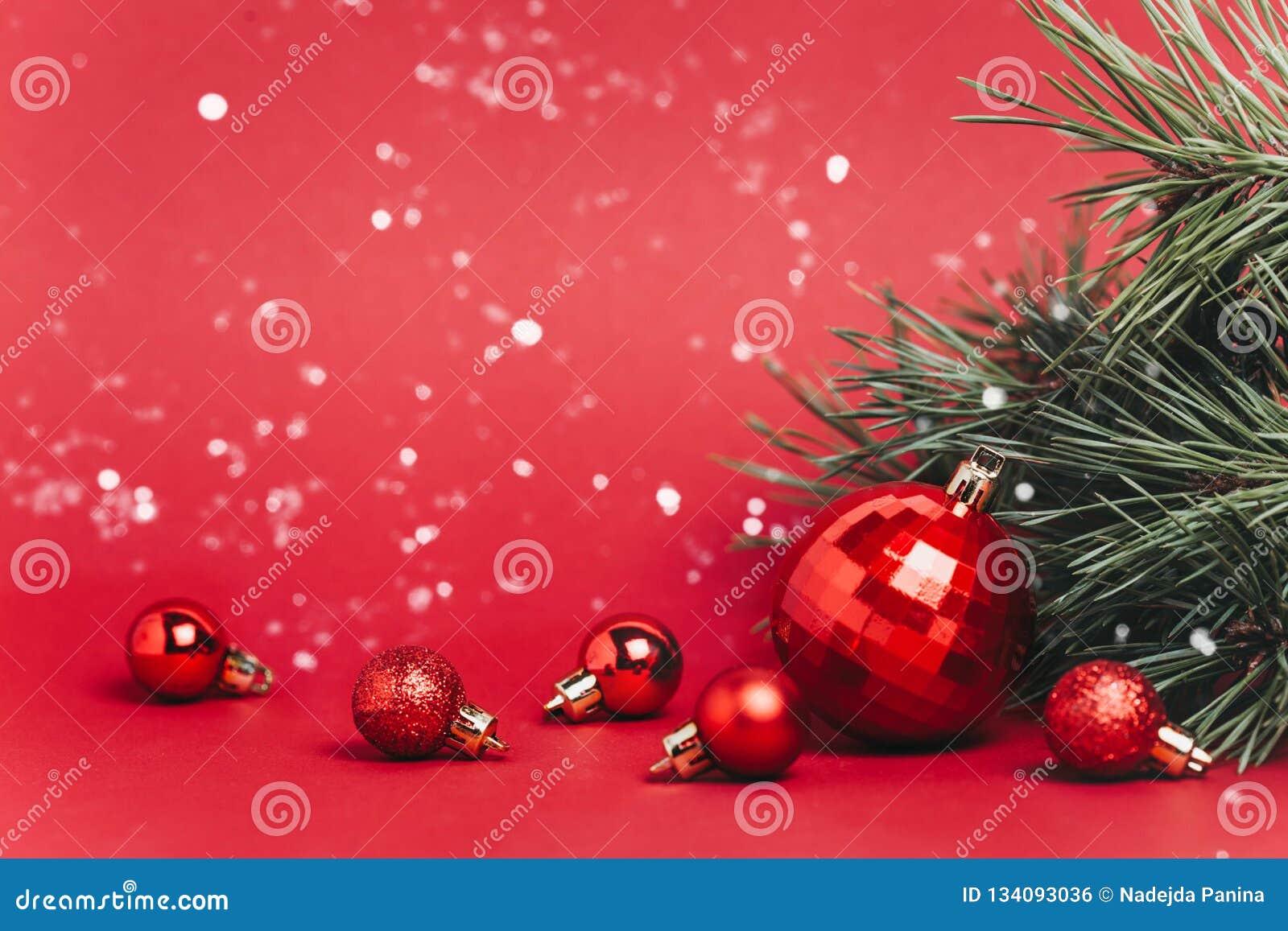与圣诞节球的圣诞节红色落在他们的背景和雪