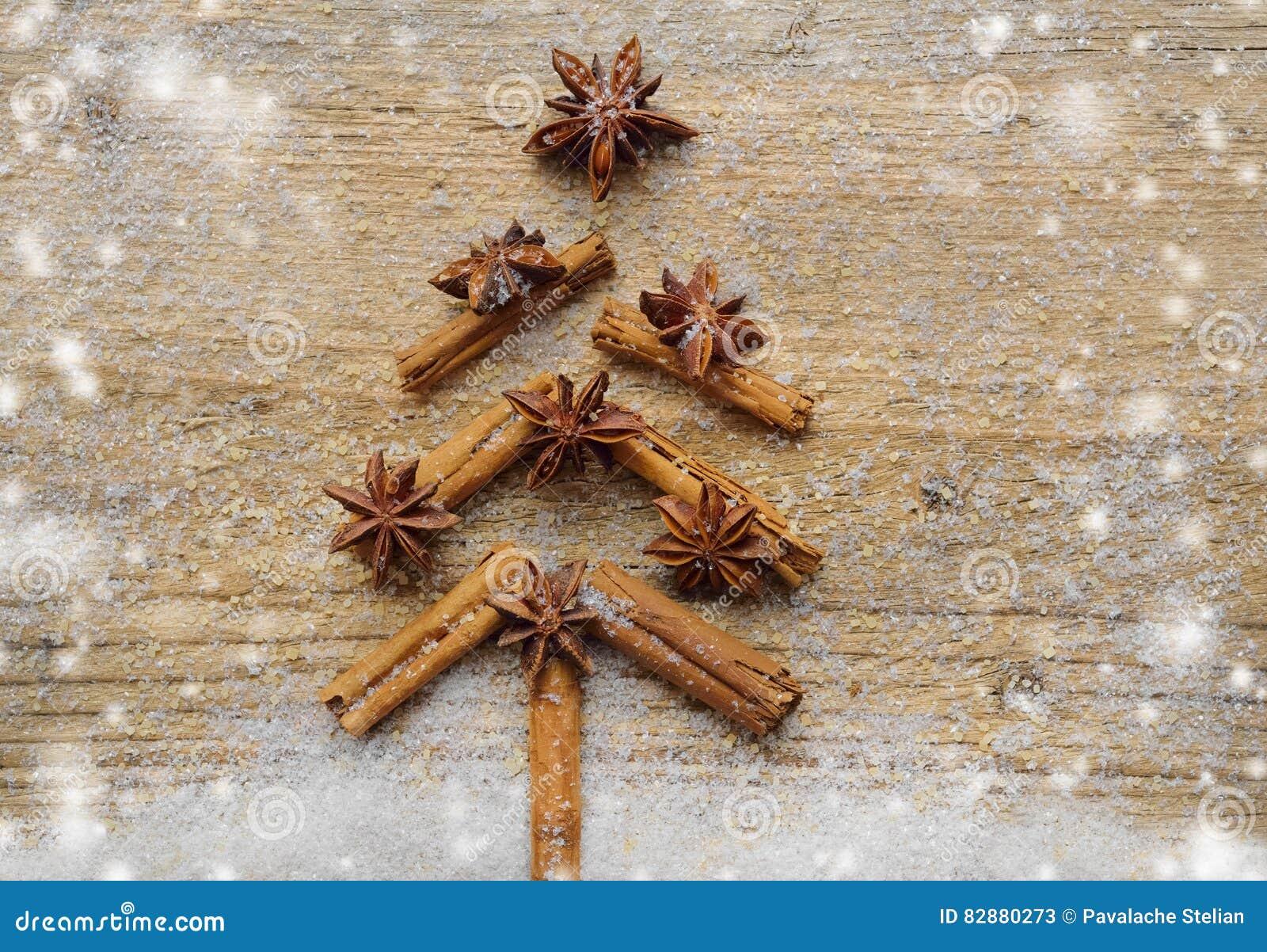 与圣诞节由香料肉桂条、茴香星和蔗糖做的杉树的圣诞卡在土气木背景