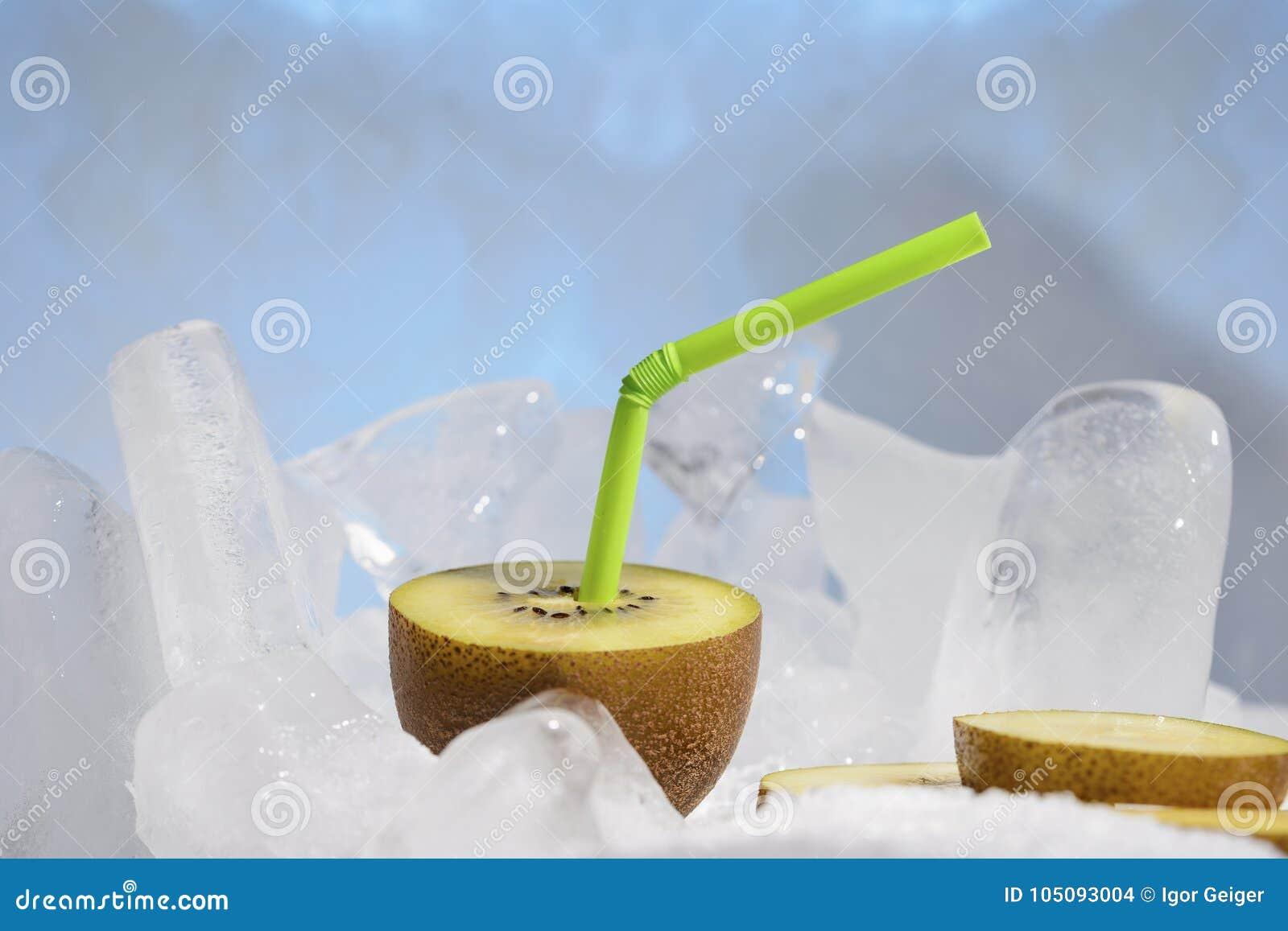 与在冷的蓝色冰结冰的鸡尾酒秸杆的新鲜的金黄猕猴桃