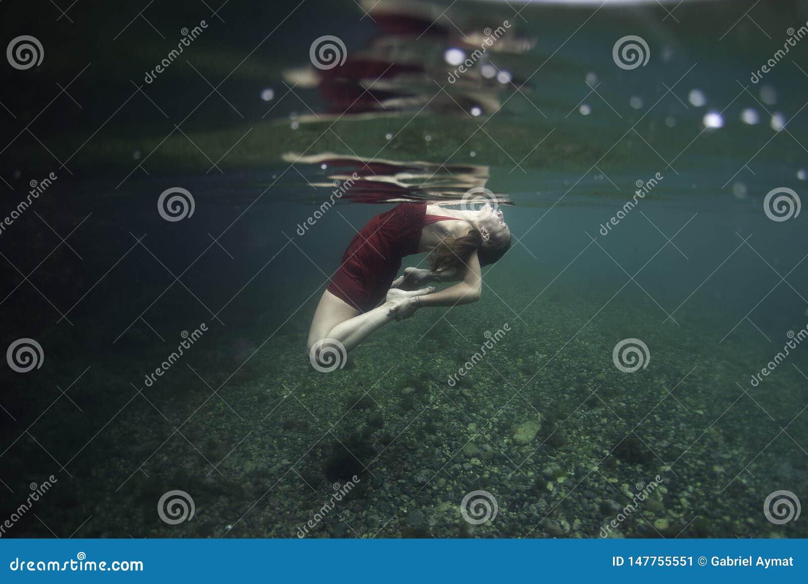 与在水面下一只红色野兽的俏丽的信奉瑜伽者跳舞