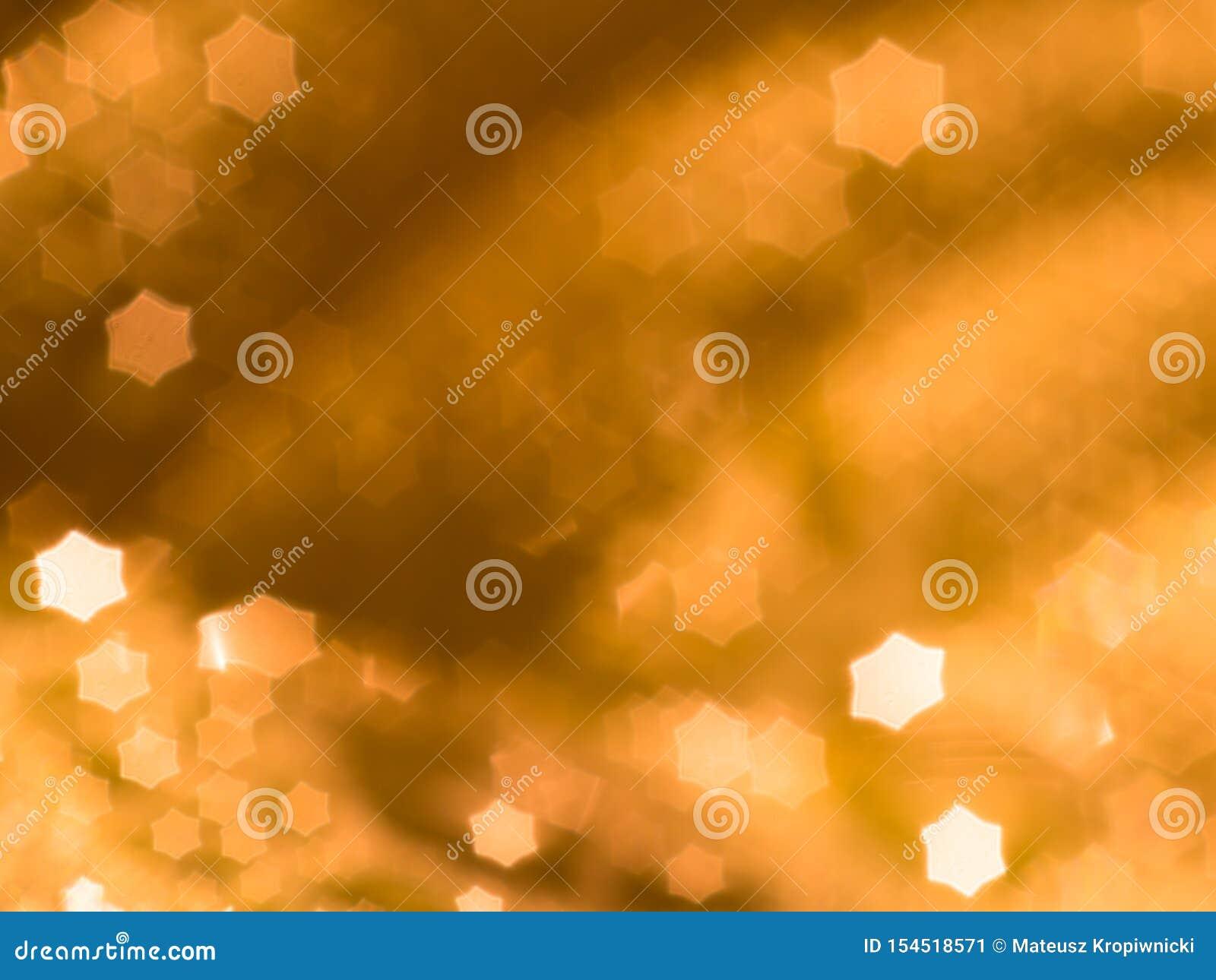 与在焦点星状bokeh球外面的橙色抽象背景