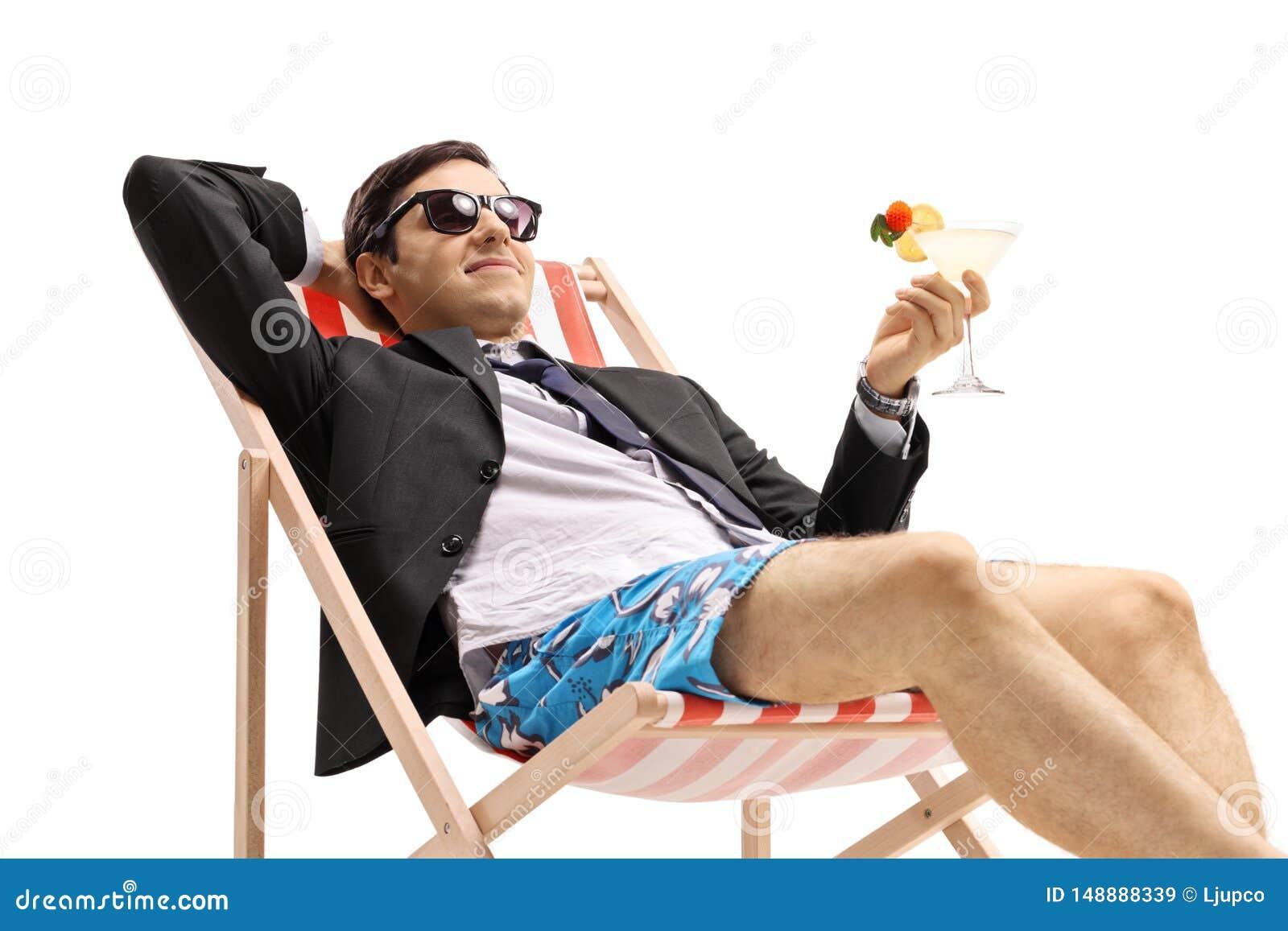 与在轻便折叠躺椅的鸡尾酒的商人