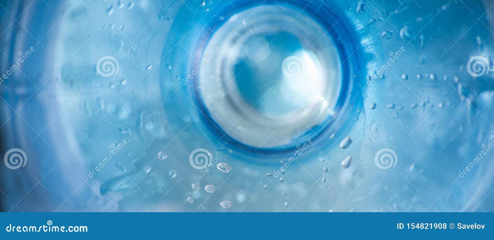 与塑料蓝色瓶表面的长的背景与水滴