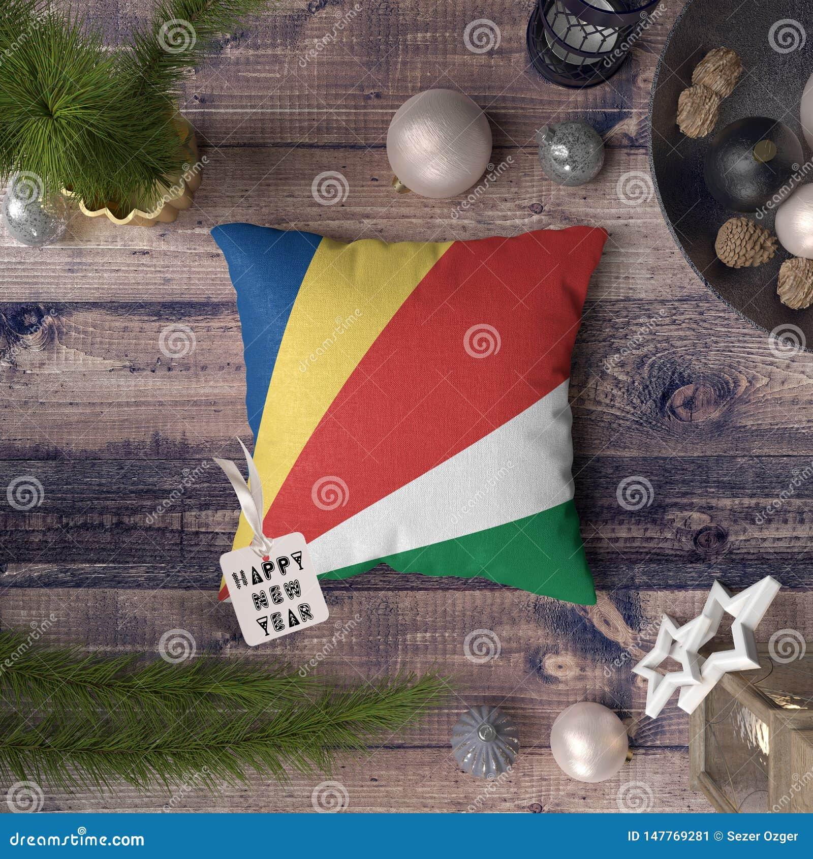 与塞舌尔旗子的新年快乐标记在枕头 在木桌上的圣诞装饰概念与可爱的对象