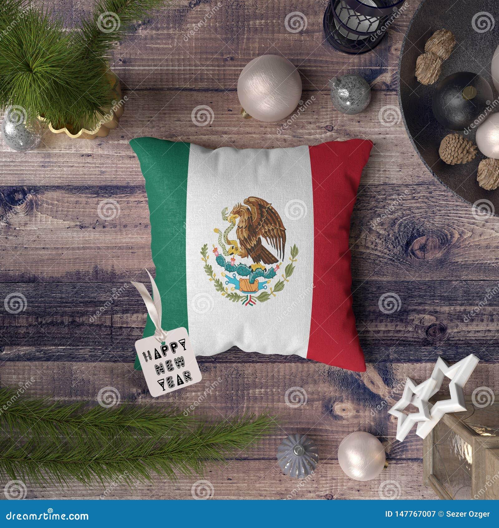 与墨西哥旗子的新年快乐标记在枕头 在木桌上的圣诞装饰概念与可爱的对象