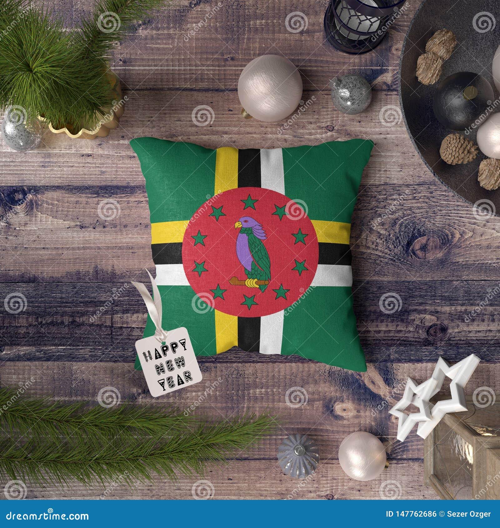 与多米尼加旗子的新年快乐标记在枕头 在木桌上的圣诞装饰概念与可爱的对象