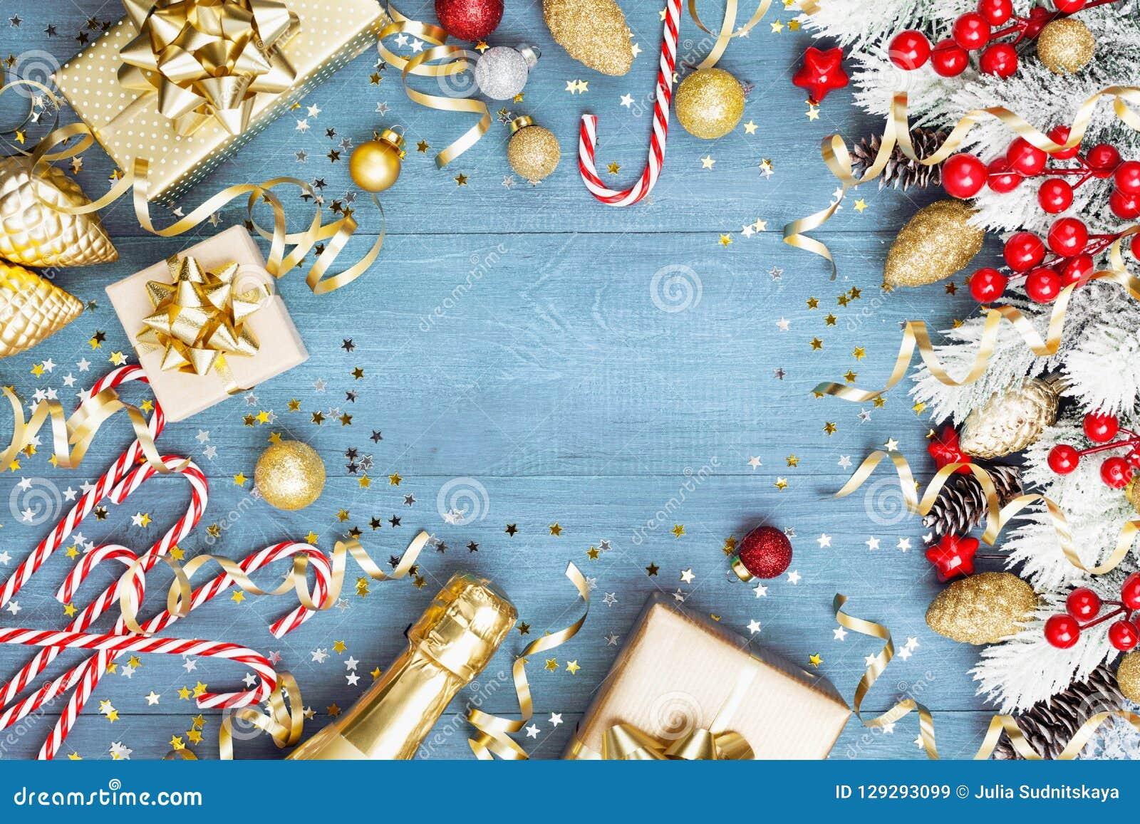 与多雪的杉树的圣诞节背景、礼物或者当前箱子、香槟和假日装饰在蓝色木台式视图