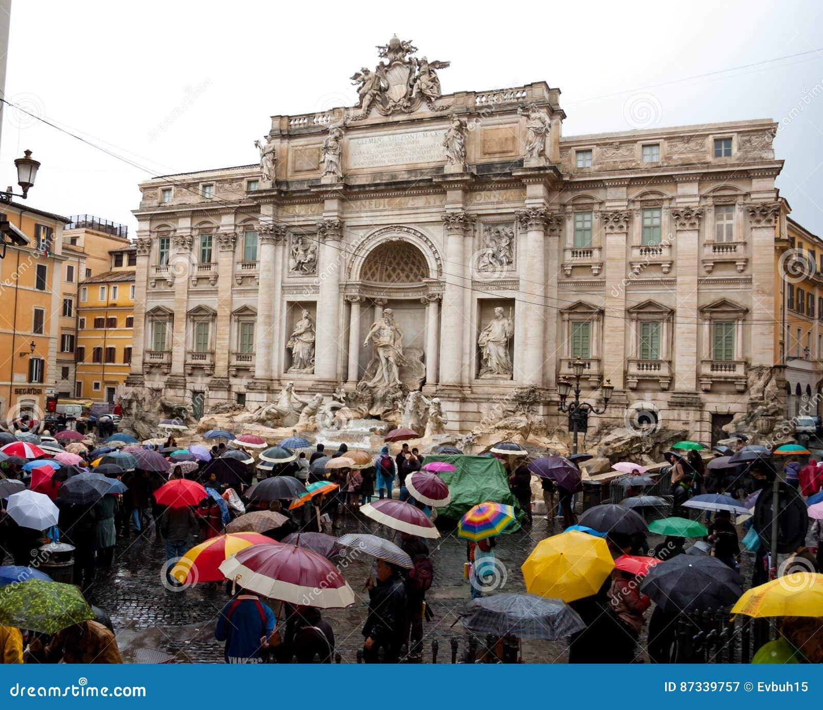 与多颜色伞的人群是常设近的Trevi喷泉