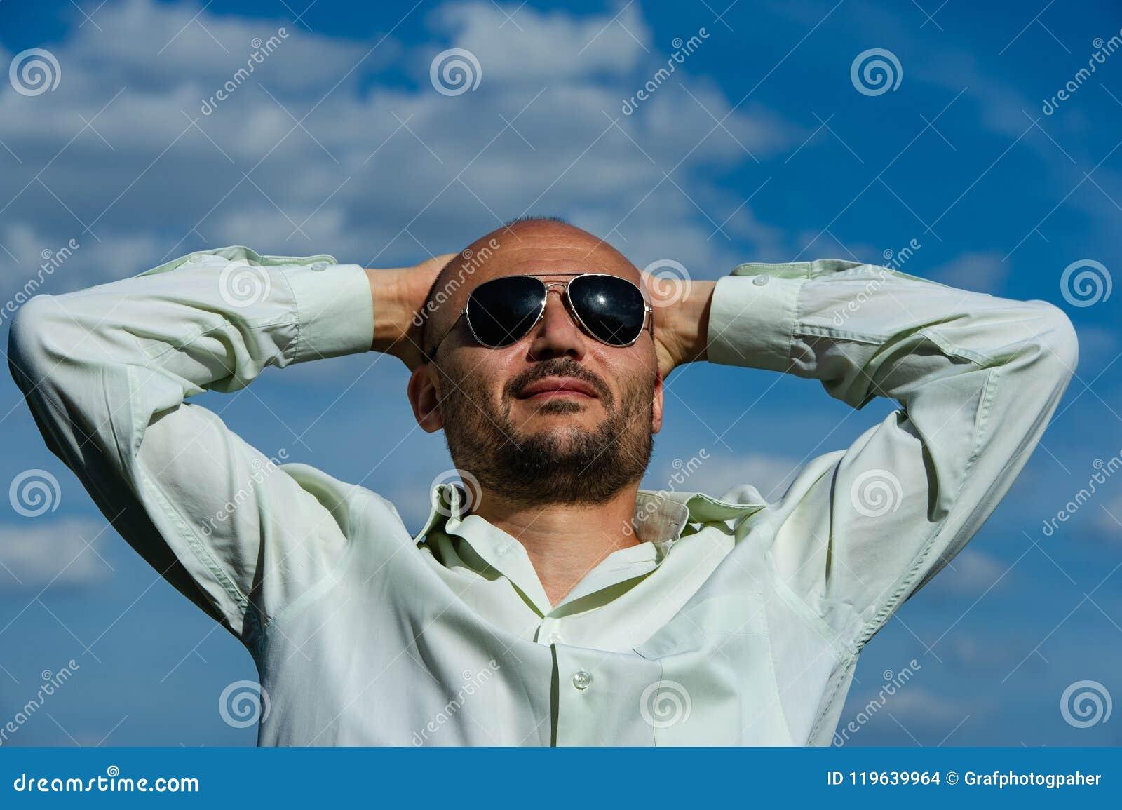 与太阳镜的有胡子的商人交叉他的在他的h后的双臂