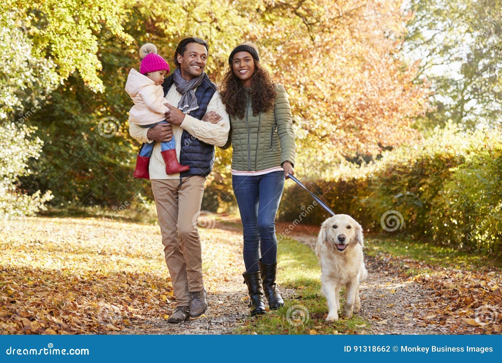 与女儿的家庭和狗享受秋天乡下步行