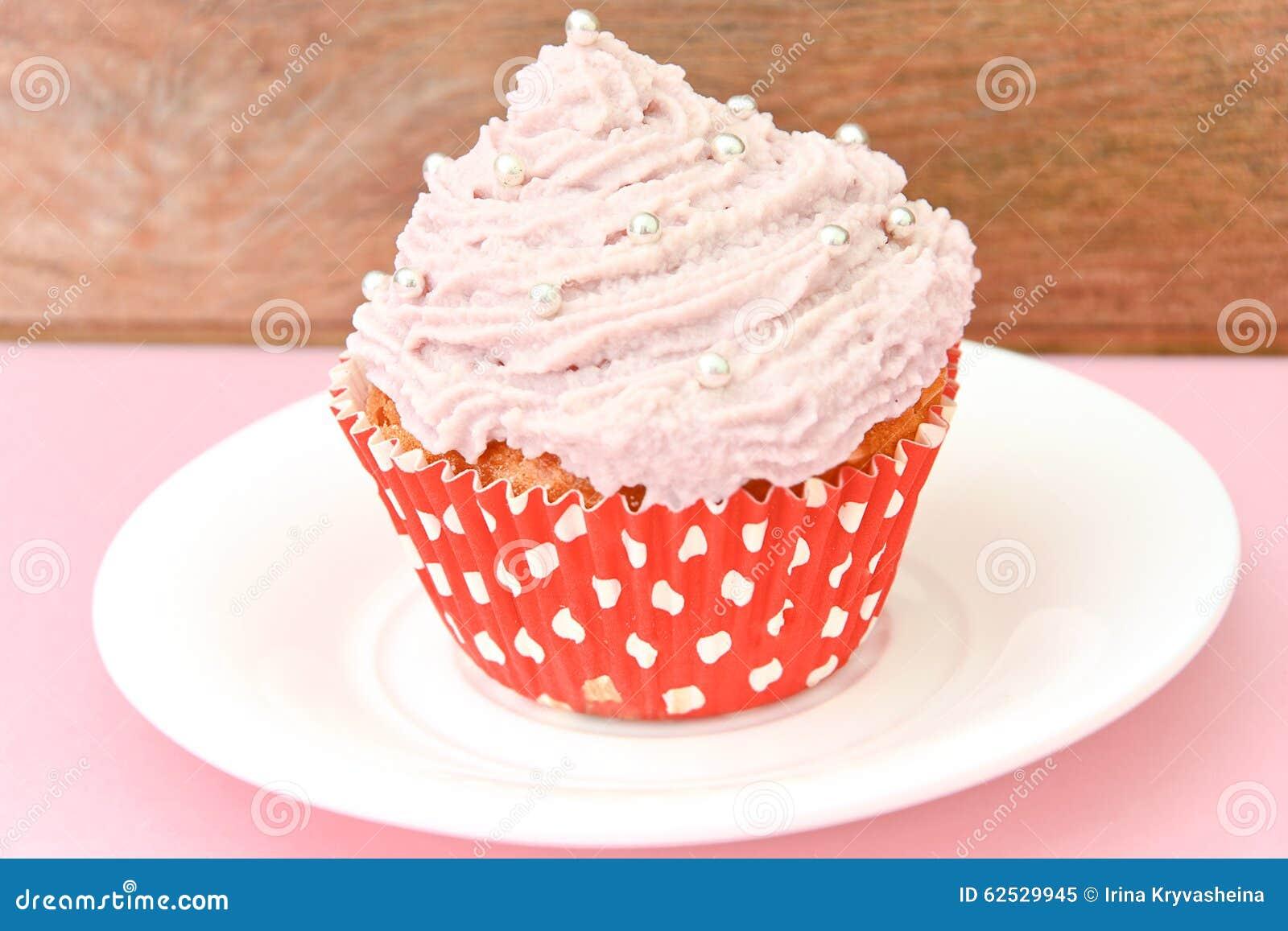 与奶油,在桃红色背景的杯形蛋糕的蛋糕