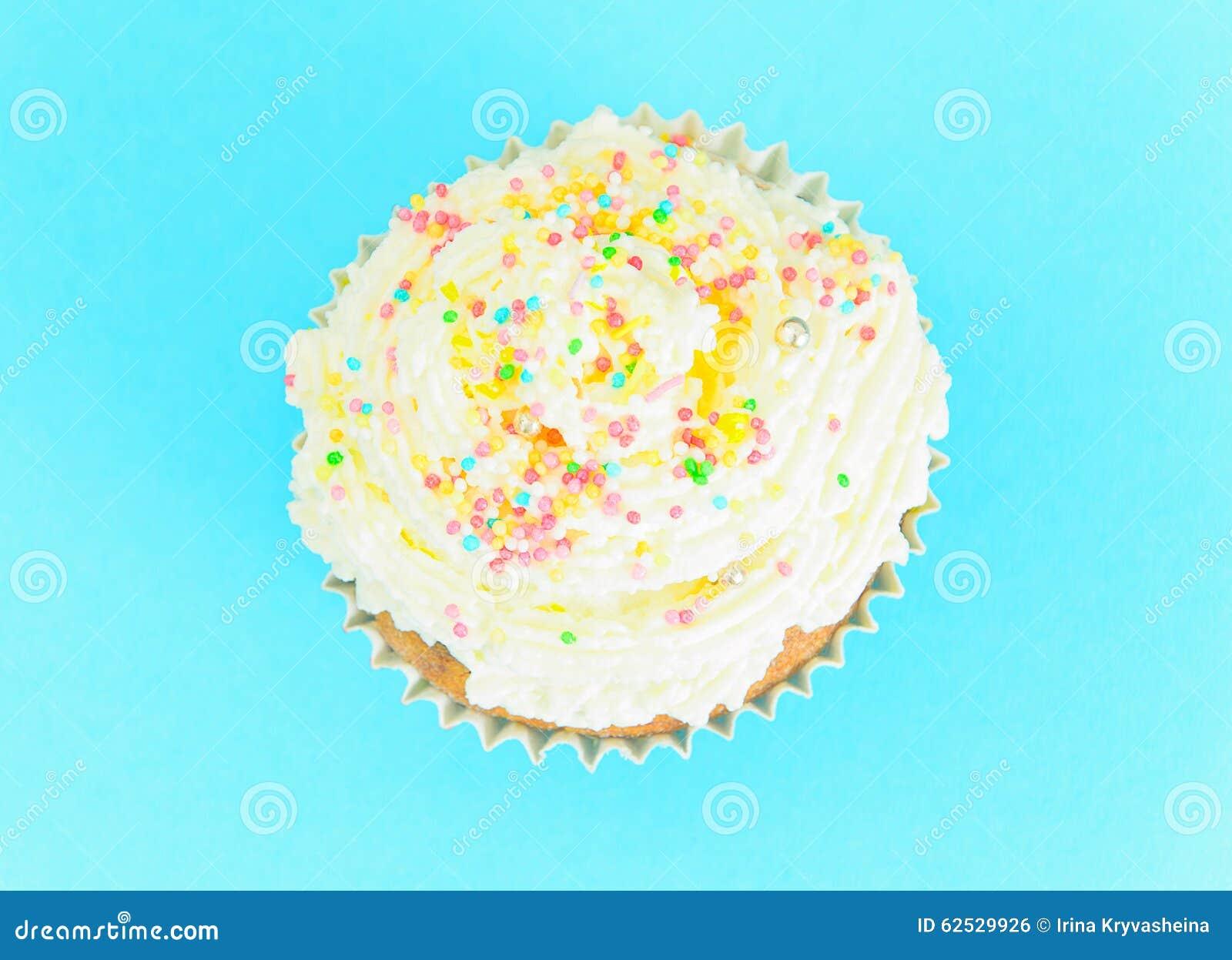 与奶油,在蓝色背景的杯形蛋糕的蛋糕