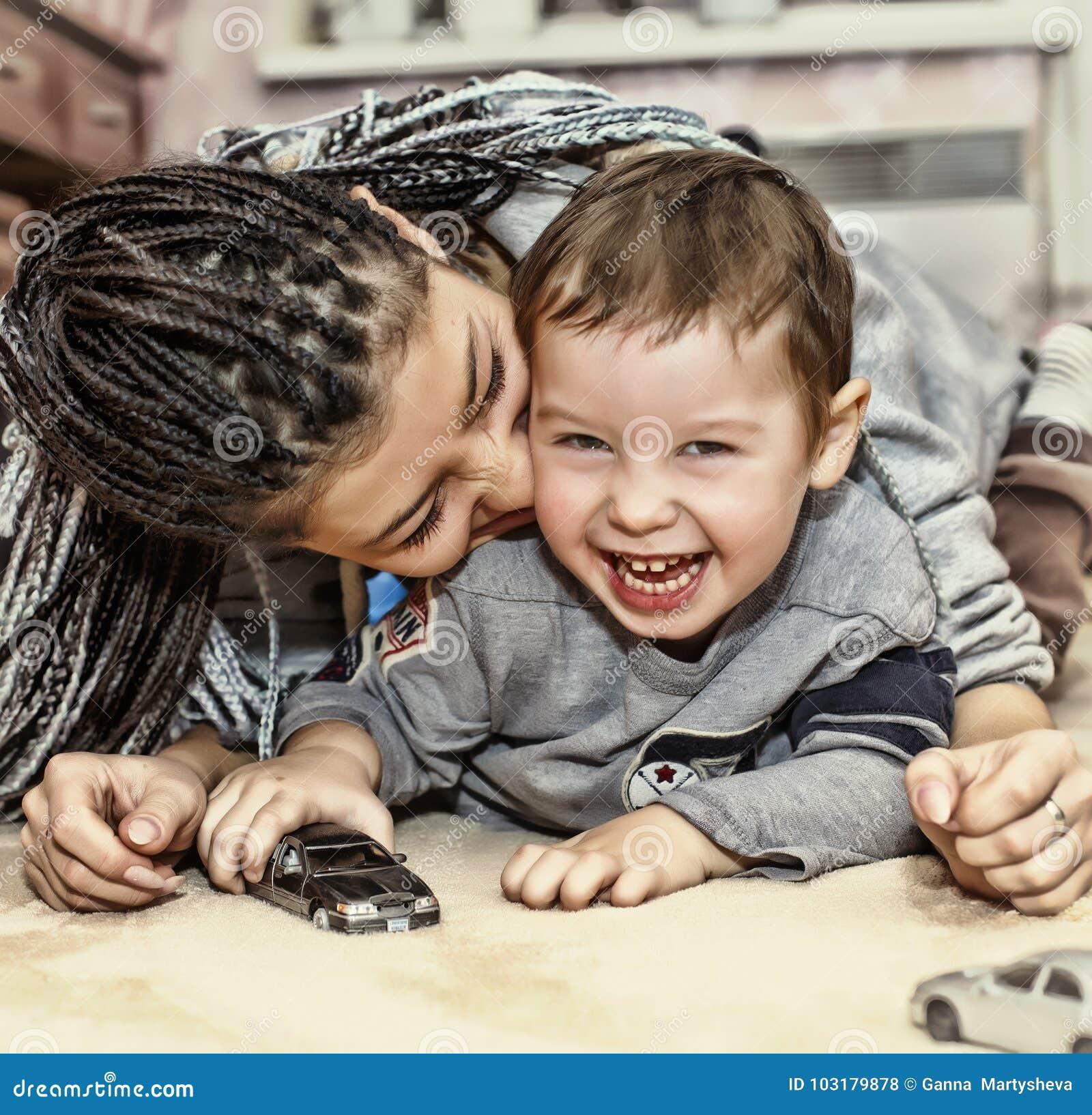与她的儿子的深色皮肤的母亲戏剧 拉丁美洲的妈妈使用并且笑与他的小儿子 概念:愉快的母亲` s天