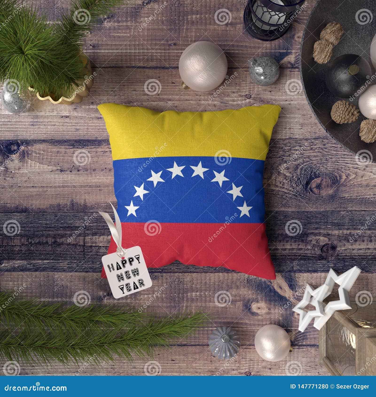 与委内瑞拉旗子的新年快乐标记在枕头 在木桌上的圣诞装饰概念与可爱的对象