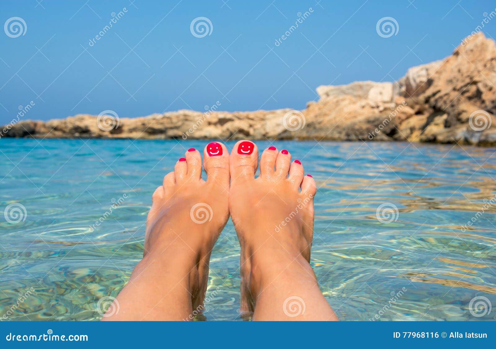 与嬉戏的面带笑容的修脚 在天蓝色的海水的女性脚