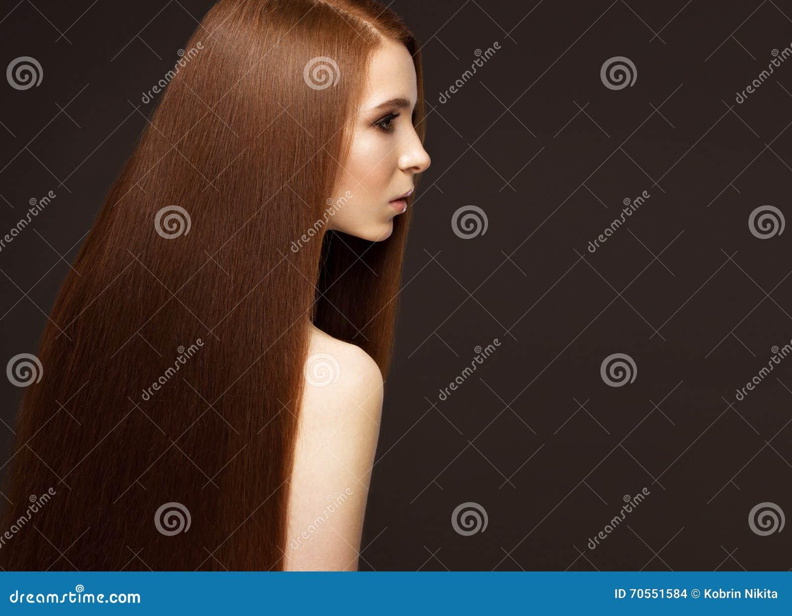 与完全光滑的头发和经典构成的美丽的Redheadgirl 秀丽表面